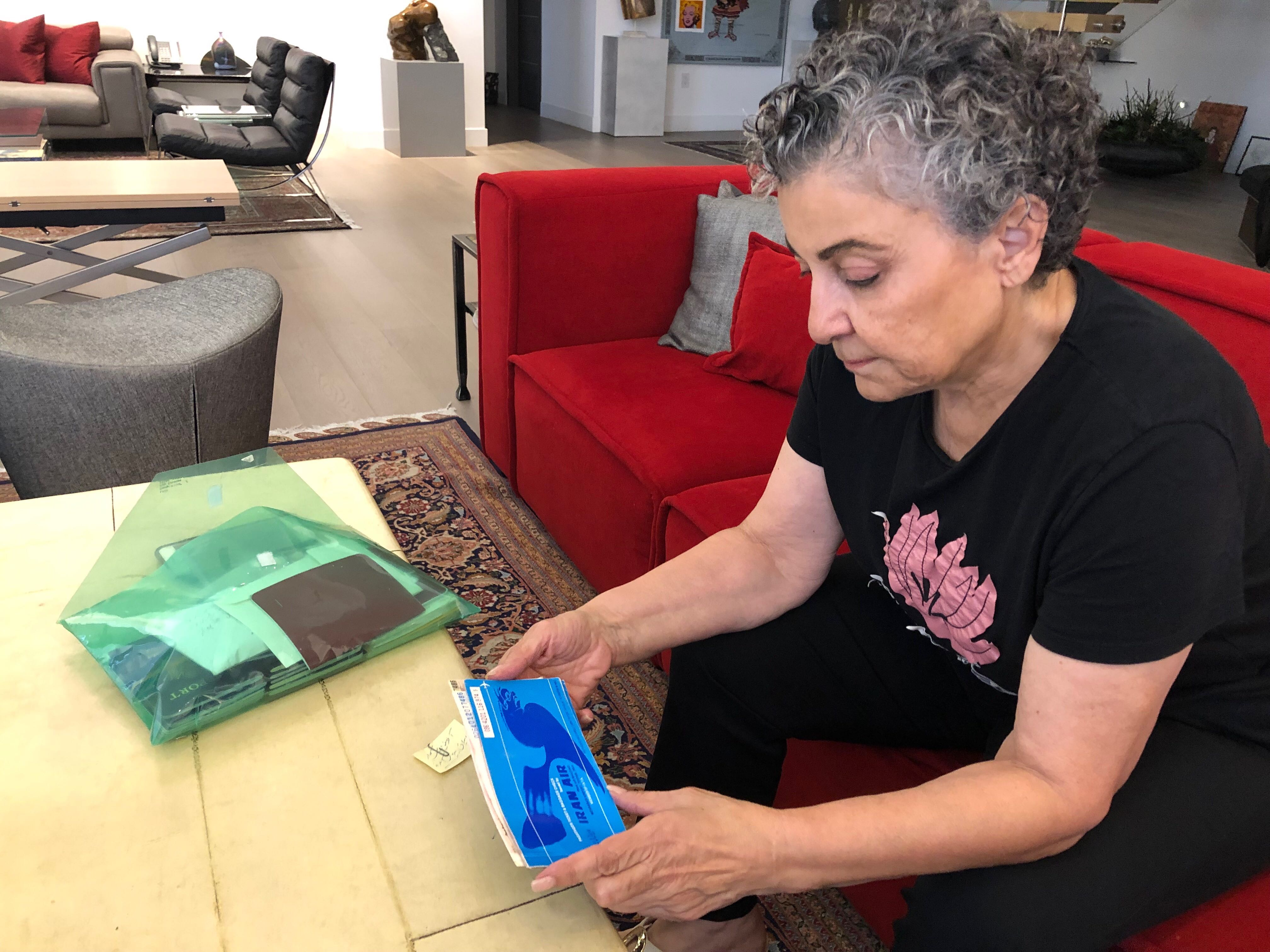 Iranian American radio host Homa Sarsharat her home in Los Angeles. She holds the plane ticket that brought her to the US more than 40 years ago.