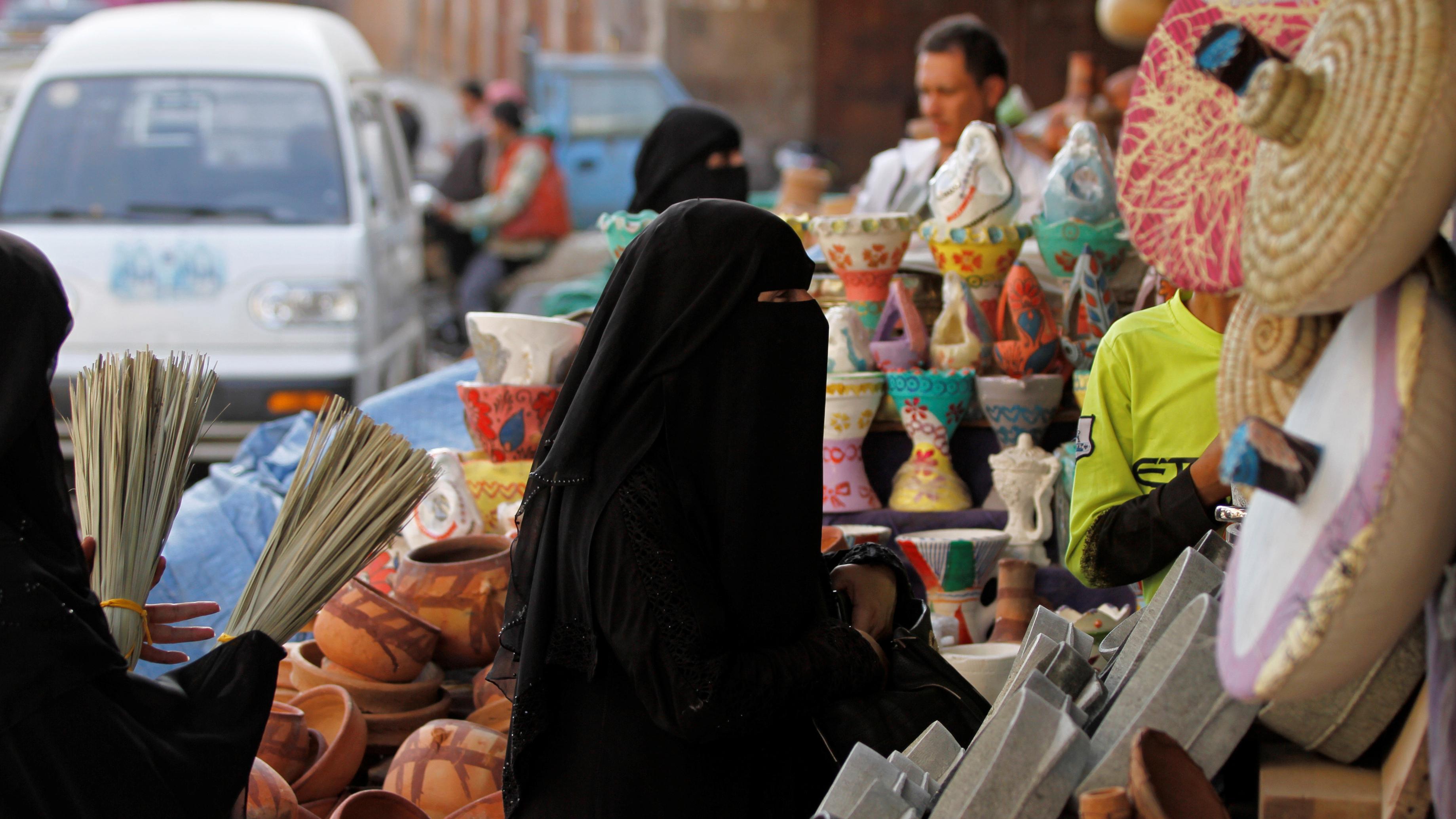Women in black hijab shop at market in Sanaa, Yemen