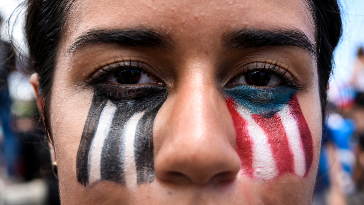 A woman with a Puerto Rican flag painted on her face looks at the camera.