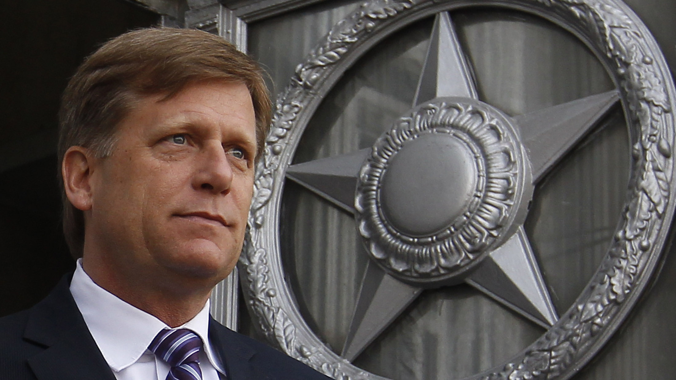 Close up of a white man in front of a star emblem