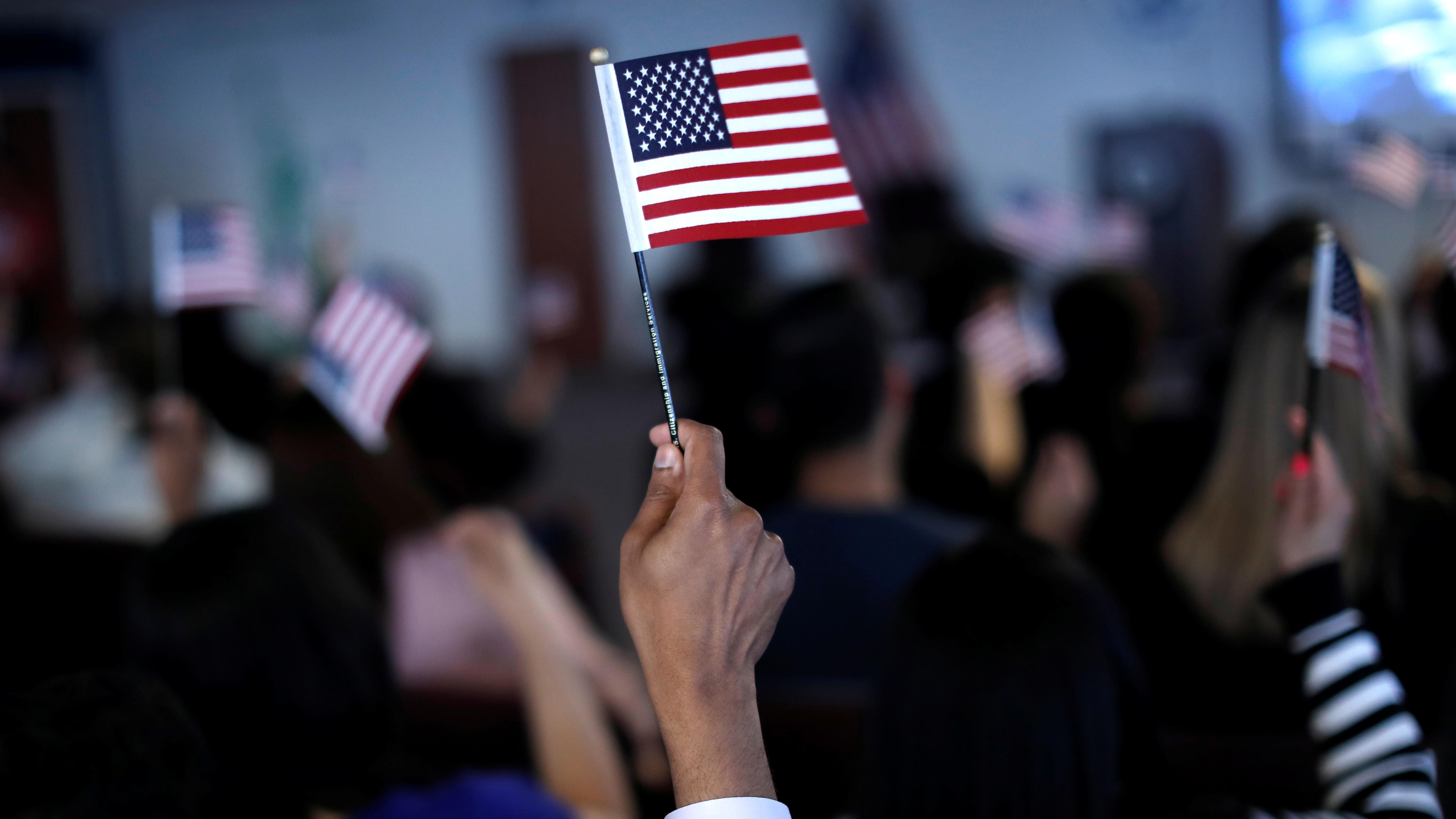 A hand waving a small American flag