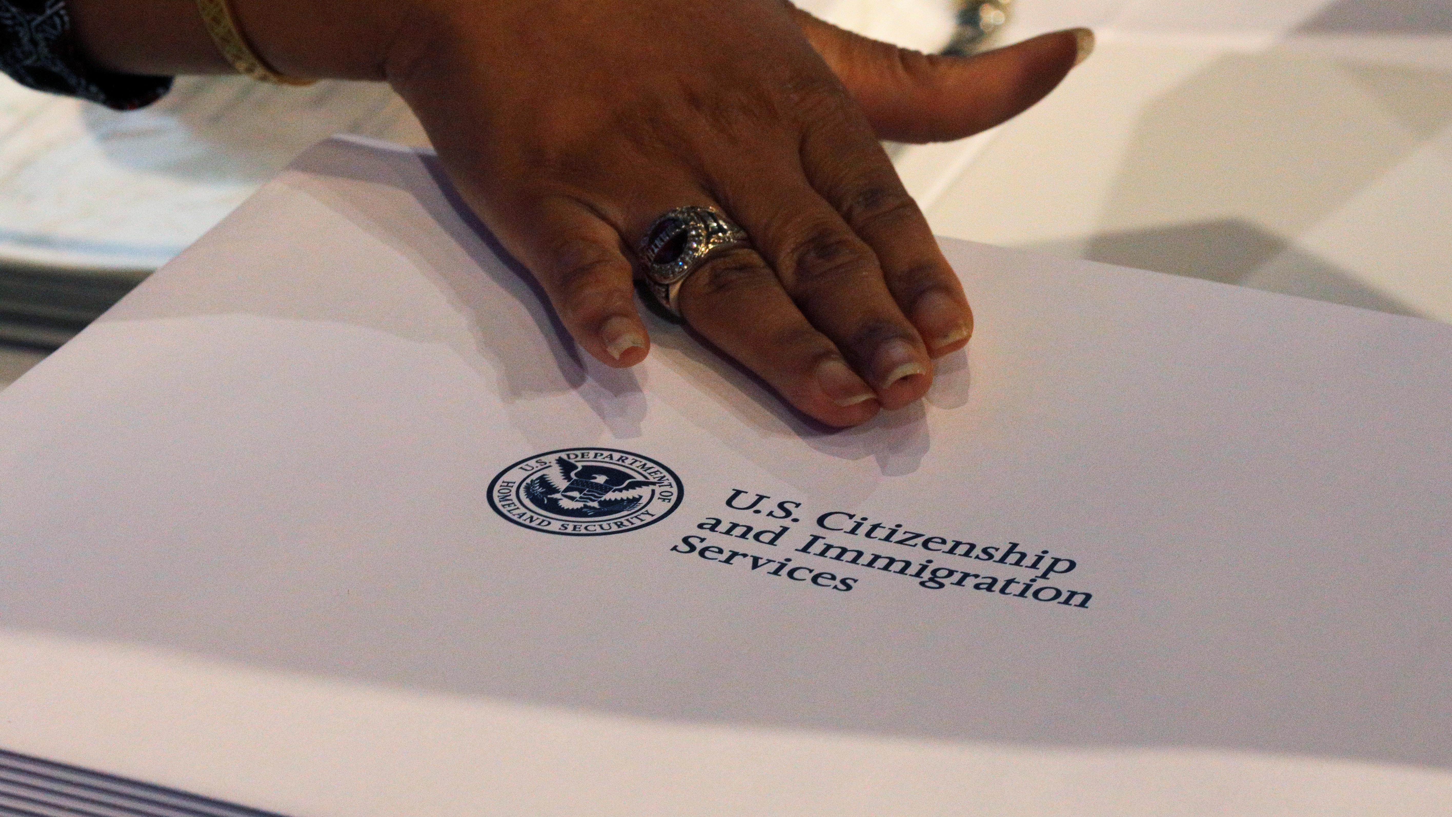 A close up of a hand and a USCIS folder