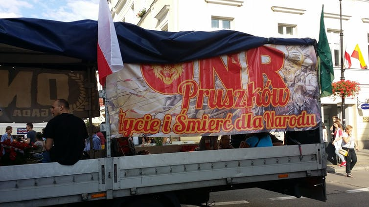 A truck with a sign on it written in Polish