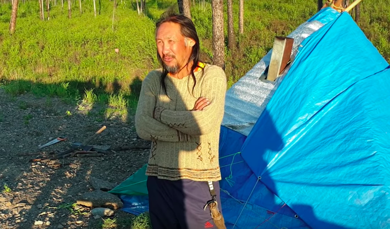 A man stands outside next to a tent.