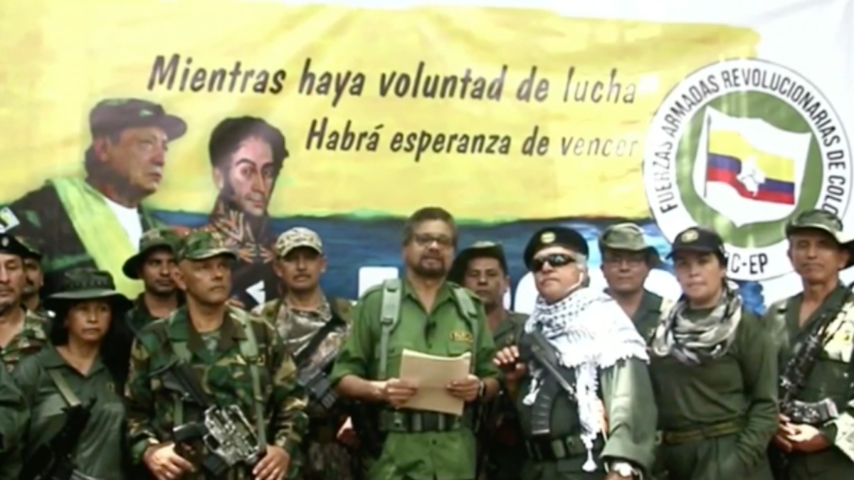 A group of men and women, some holding arms stand around a man reading from a document.