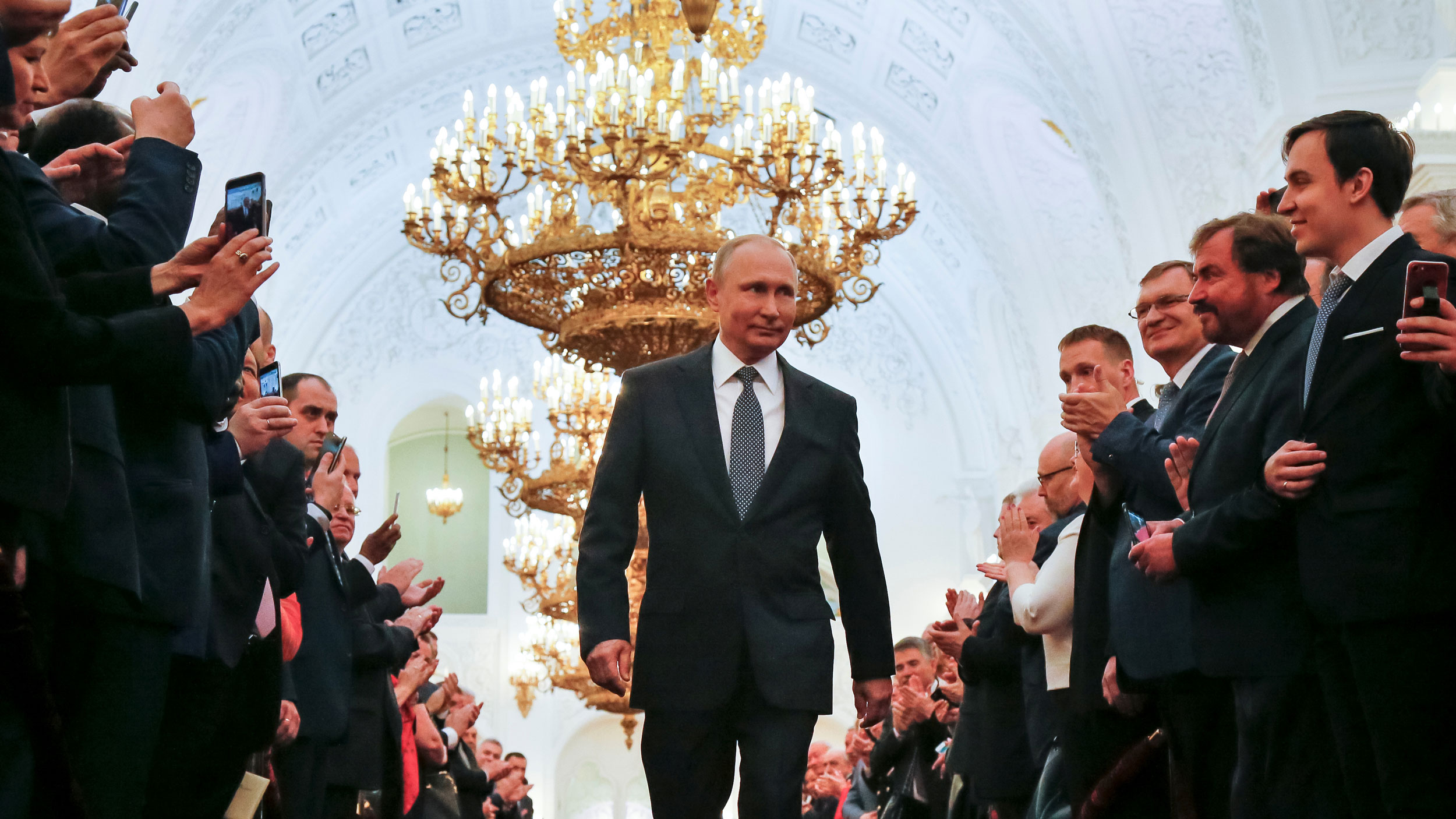 Vladimir Putin walks between two rows of people clapping their hands and taking photos with their cell phones