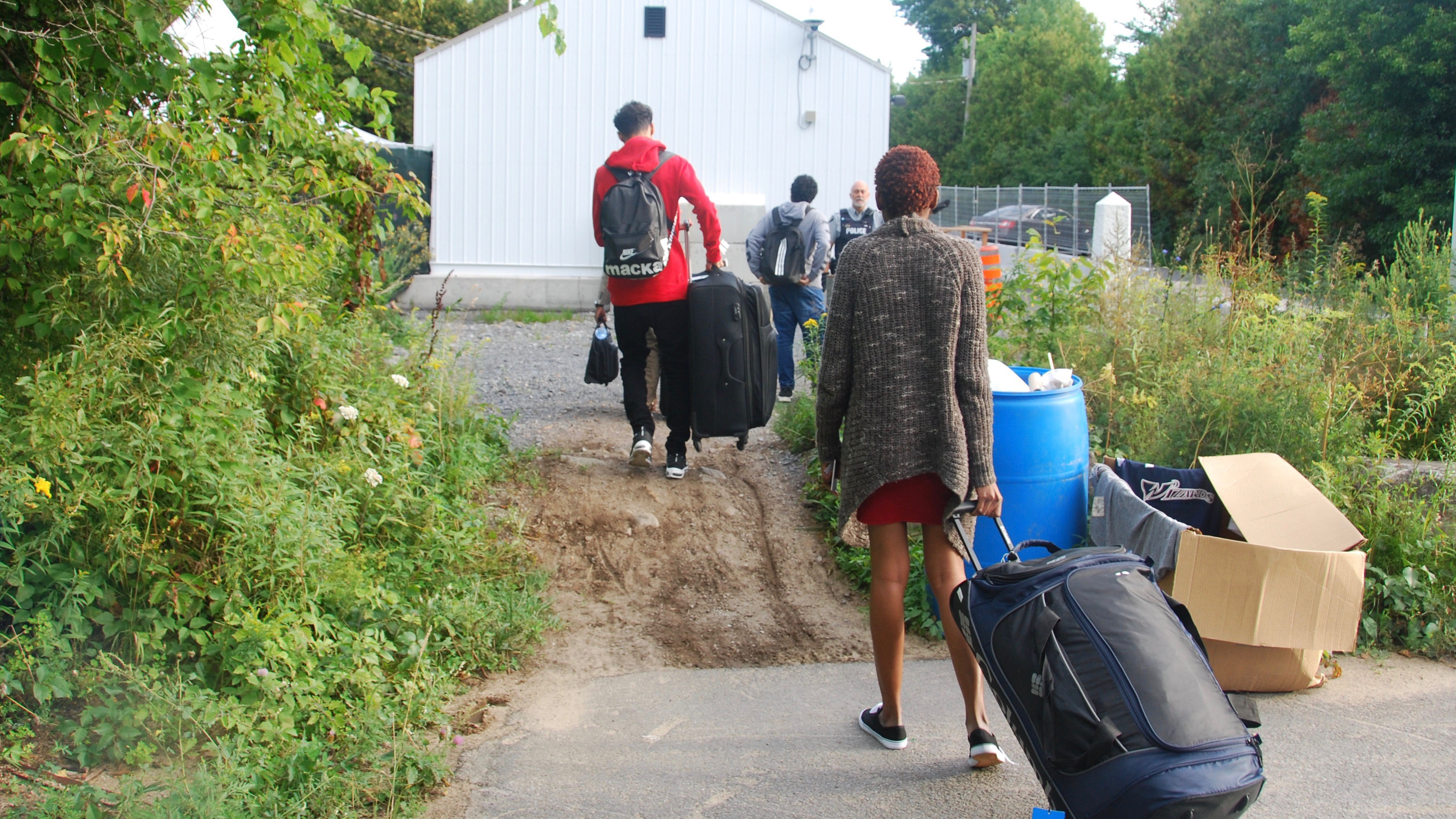 A woman drags a suitcase in the foreground. In the background, a police officer and three men dragging suitcases.