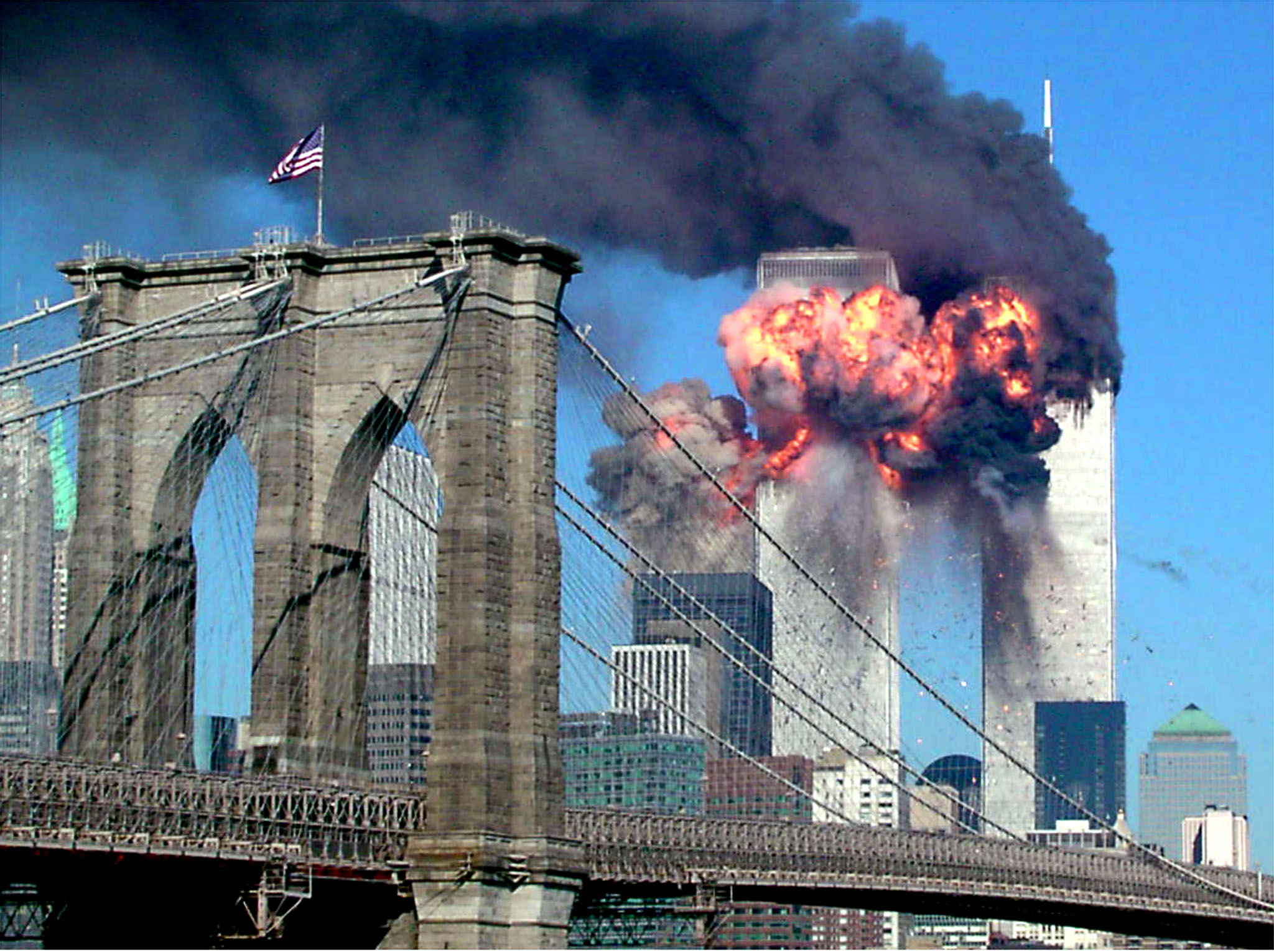 The second tower of the World Trade Centre explodes after being hit by a hijacked airplane. A bridge with an American flag flying is in the foreground.