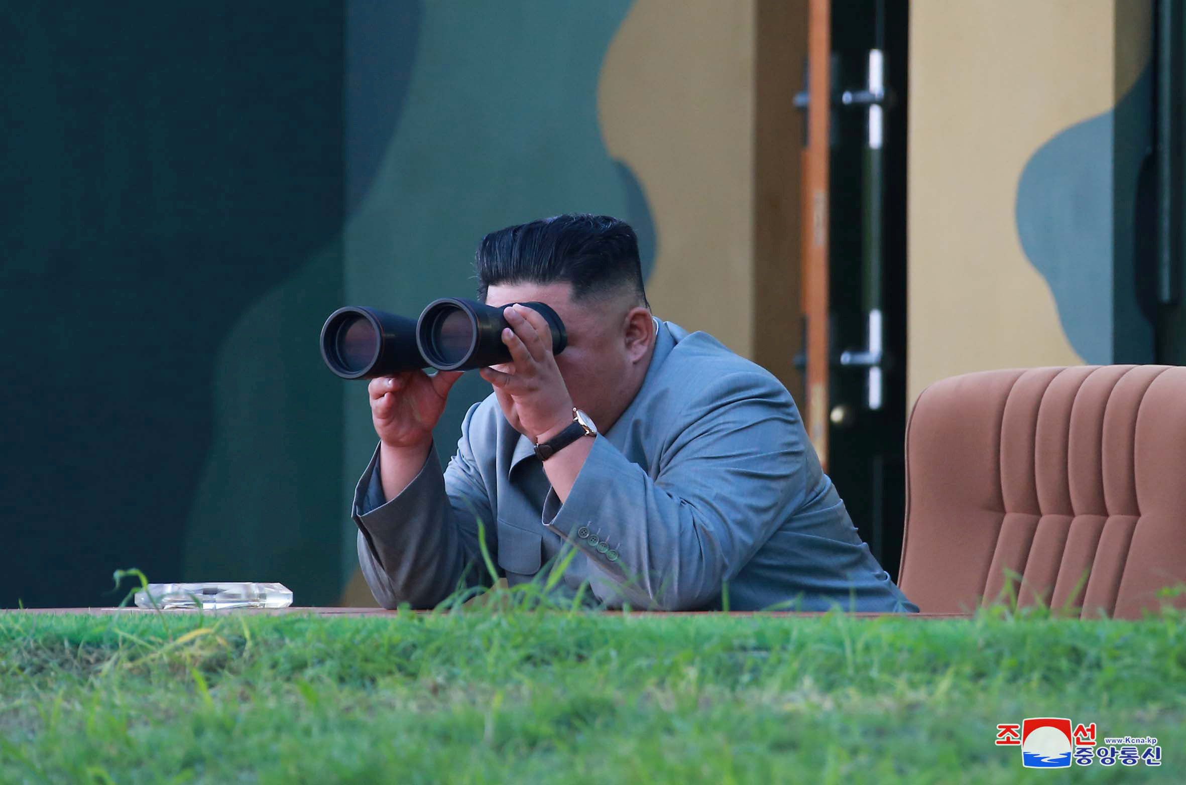 Kim Jong-un looks through binoculars and leans over a ledge