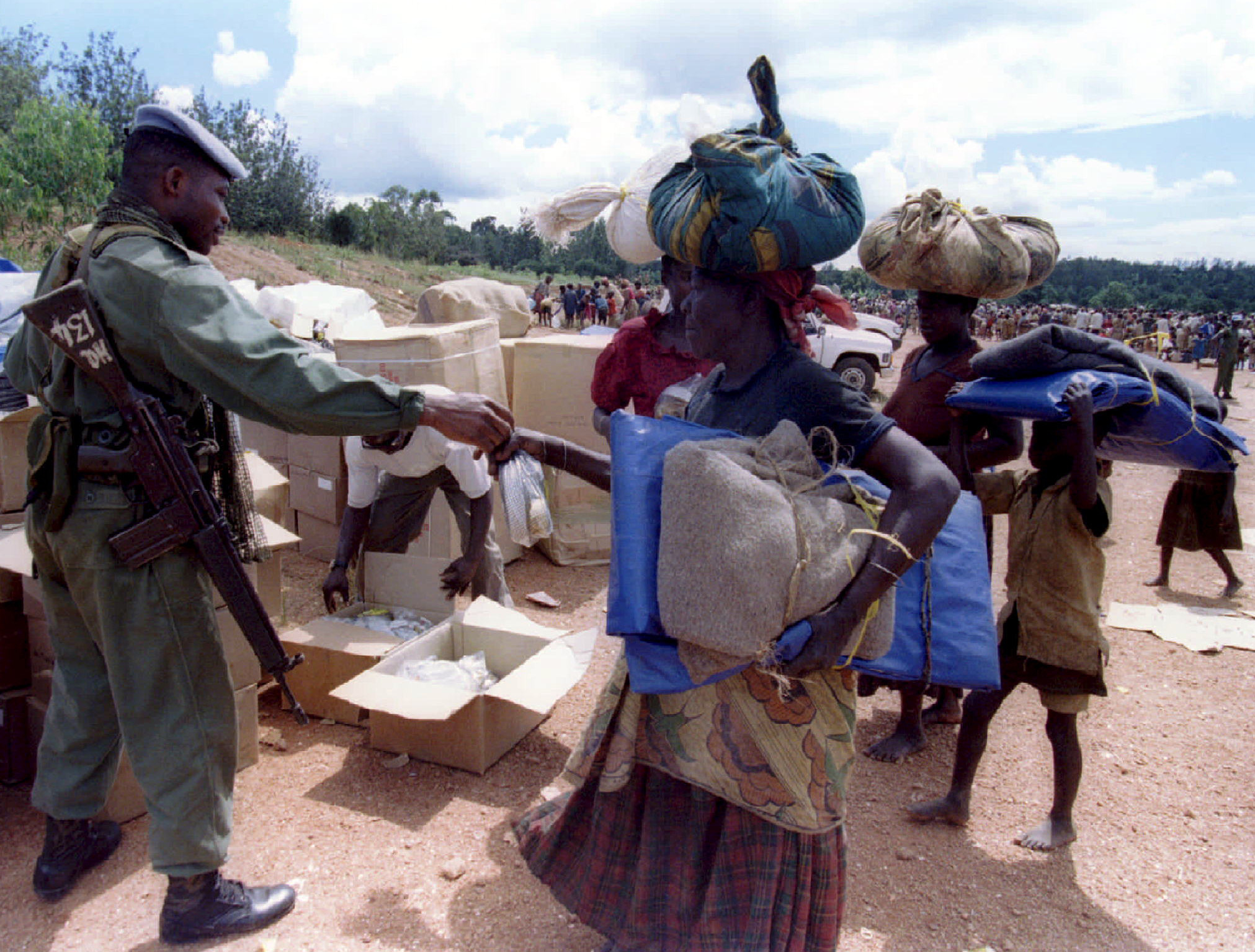 A soldier hands food to a woman.