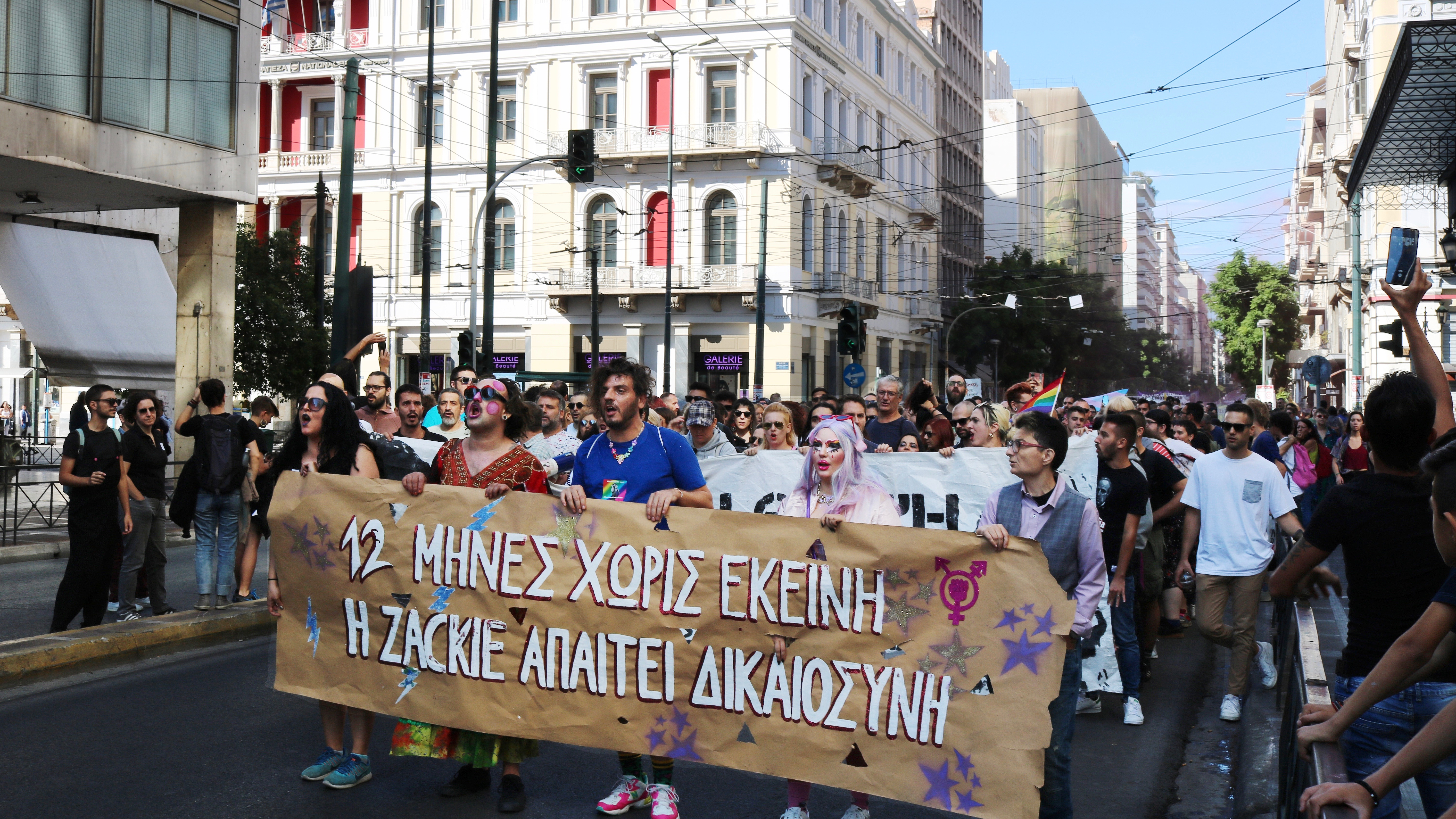 Marchers stand behind a large white banner as they move through a street