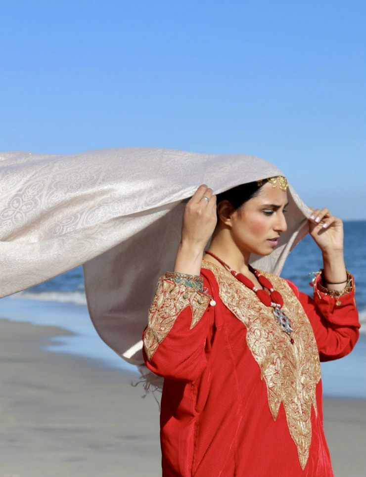 A photograph of a woman in a red pheran holding a scarf that billows out behind her