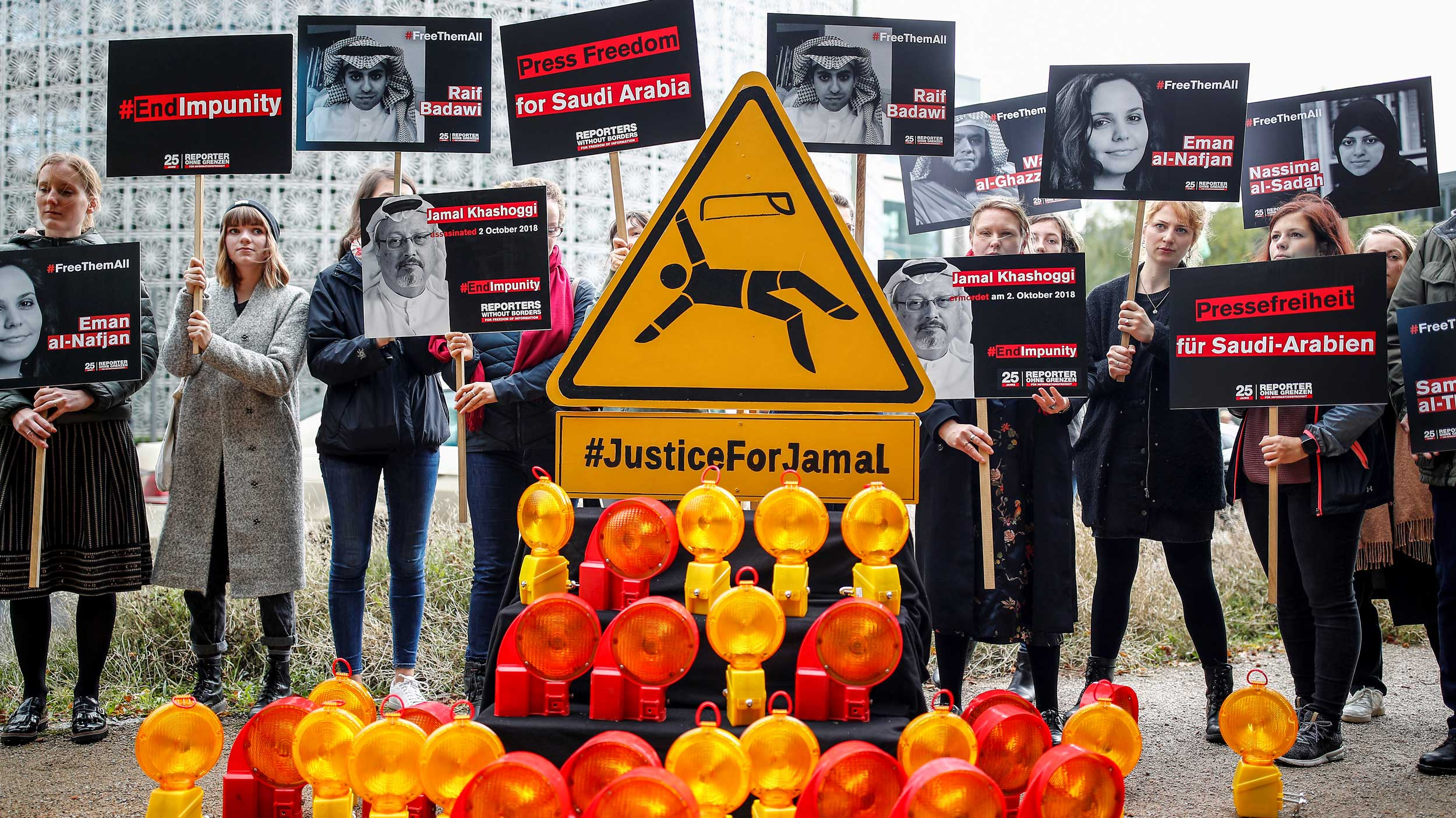Protesters hold signs with images of Saudi journalists on them