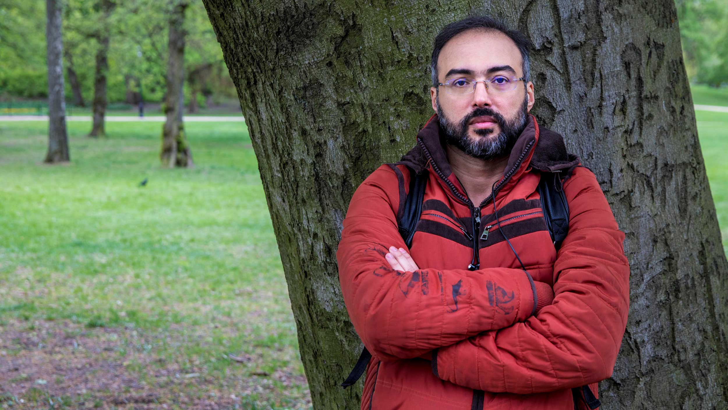 A man poses for a photo against a tree, wearing a red jacket