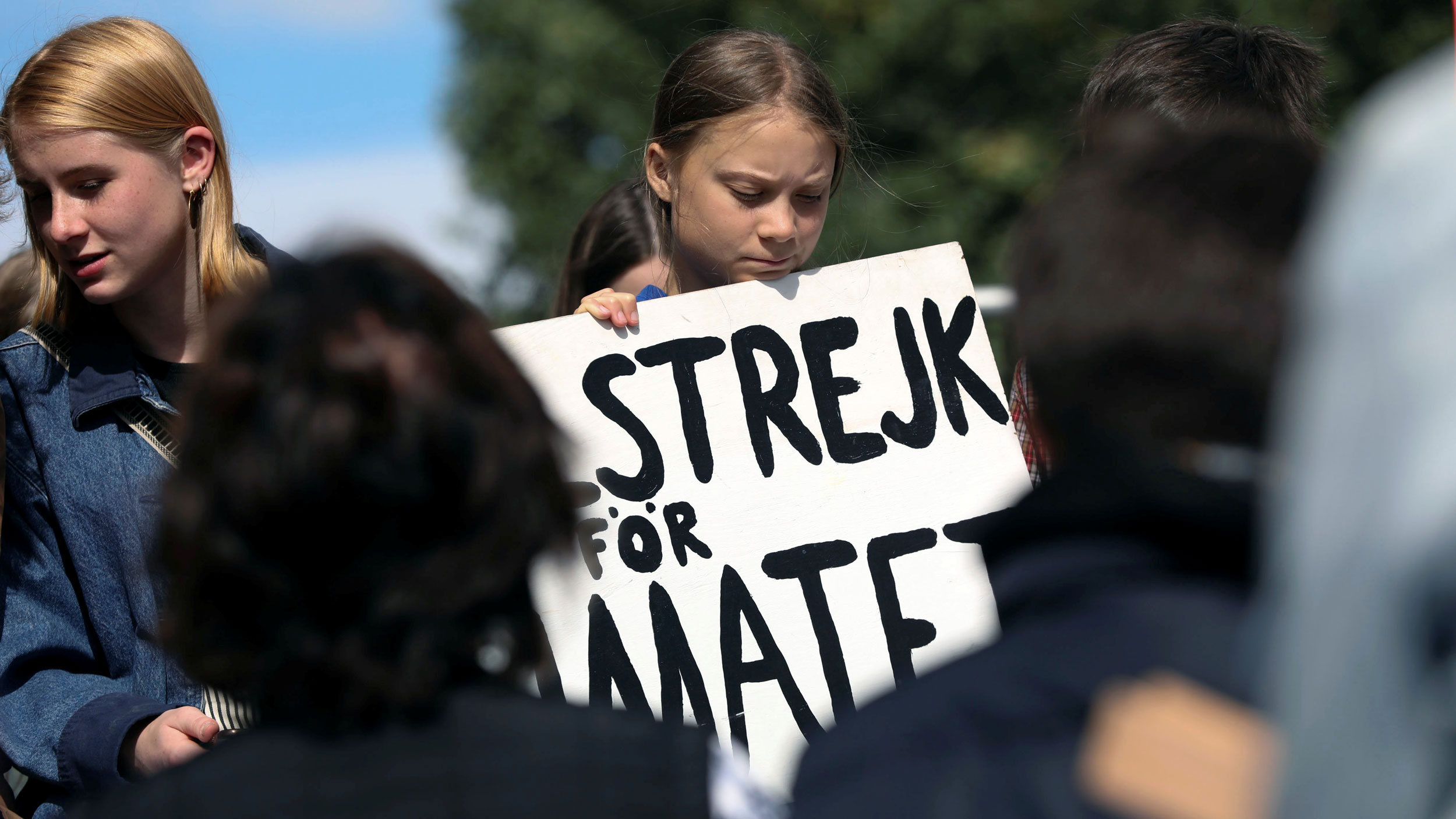 Climate change environmental teen activist Greta Thunberg participates in a climate strike rally and looks down at a placard