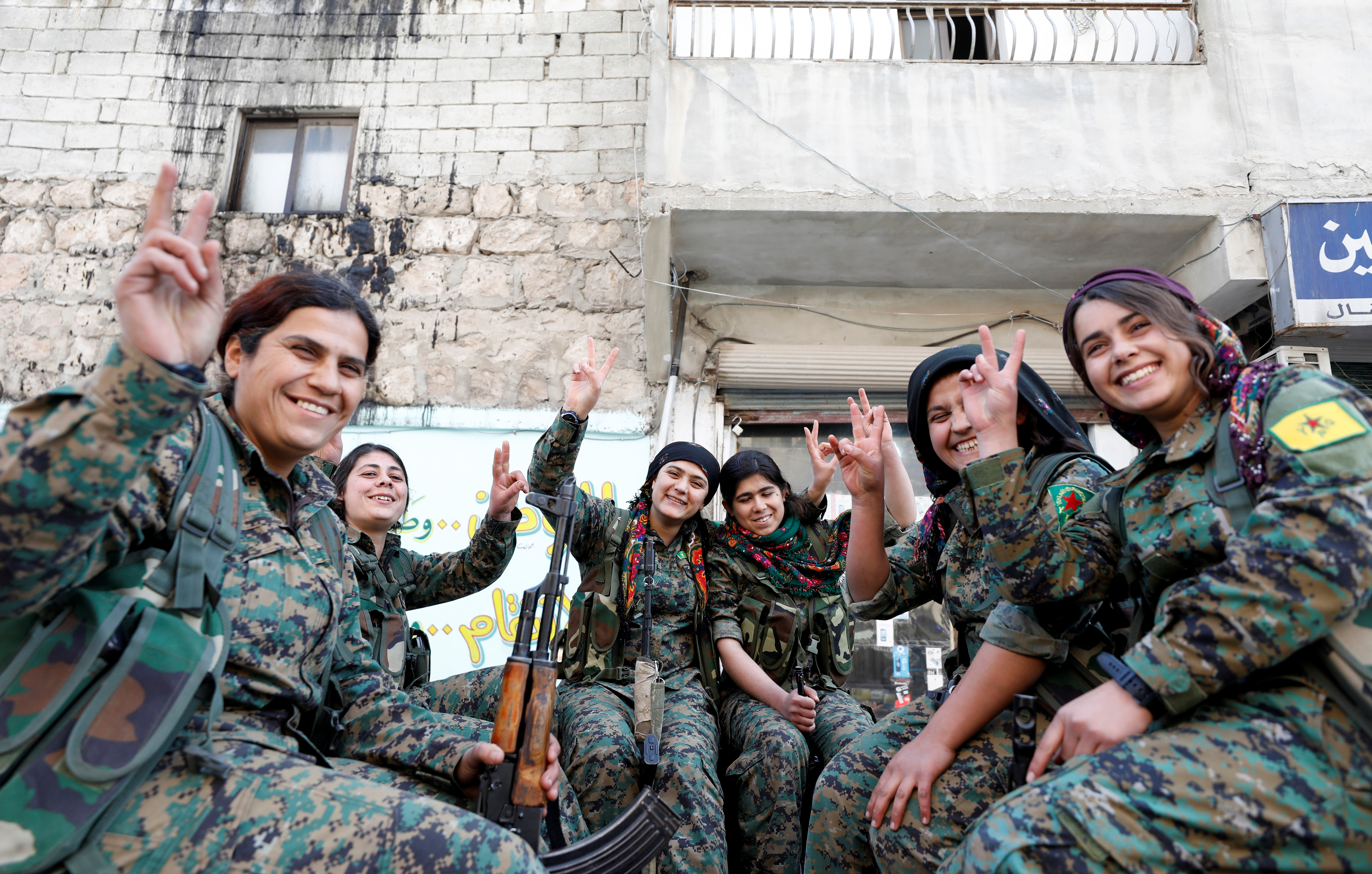 A semicircle of Kurdish female fighters of the Women's Protection Unit (YPJ) gesturing V for Victory symbols in the Sheikh Maksoud neighbourhood of Aleppo, Syria, on Feb. 7, 2018.
