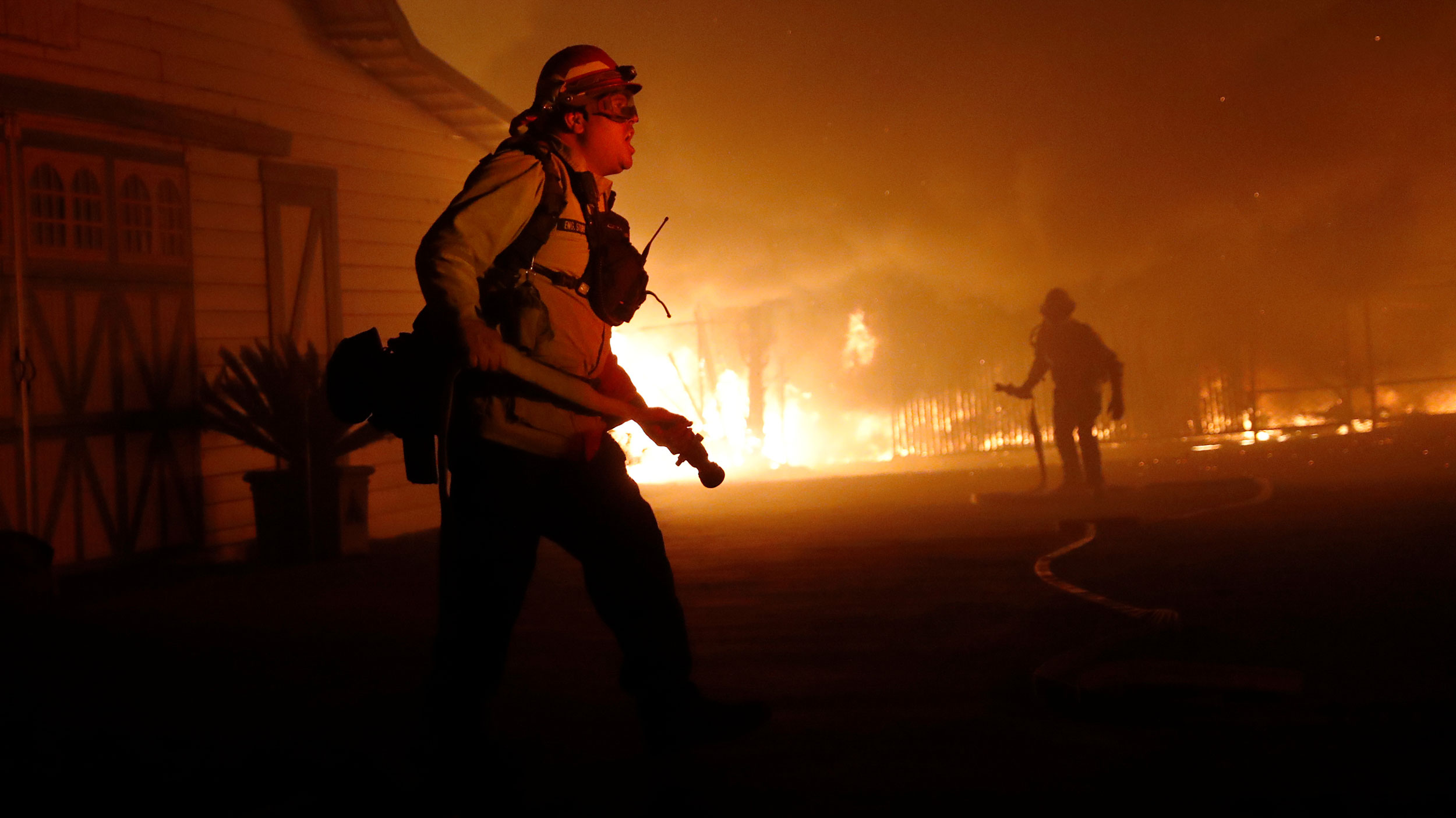 A firefighter is shown in the nearground with a barn and other buildings are on fire in the background.