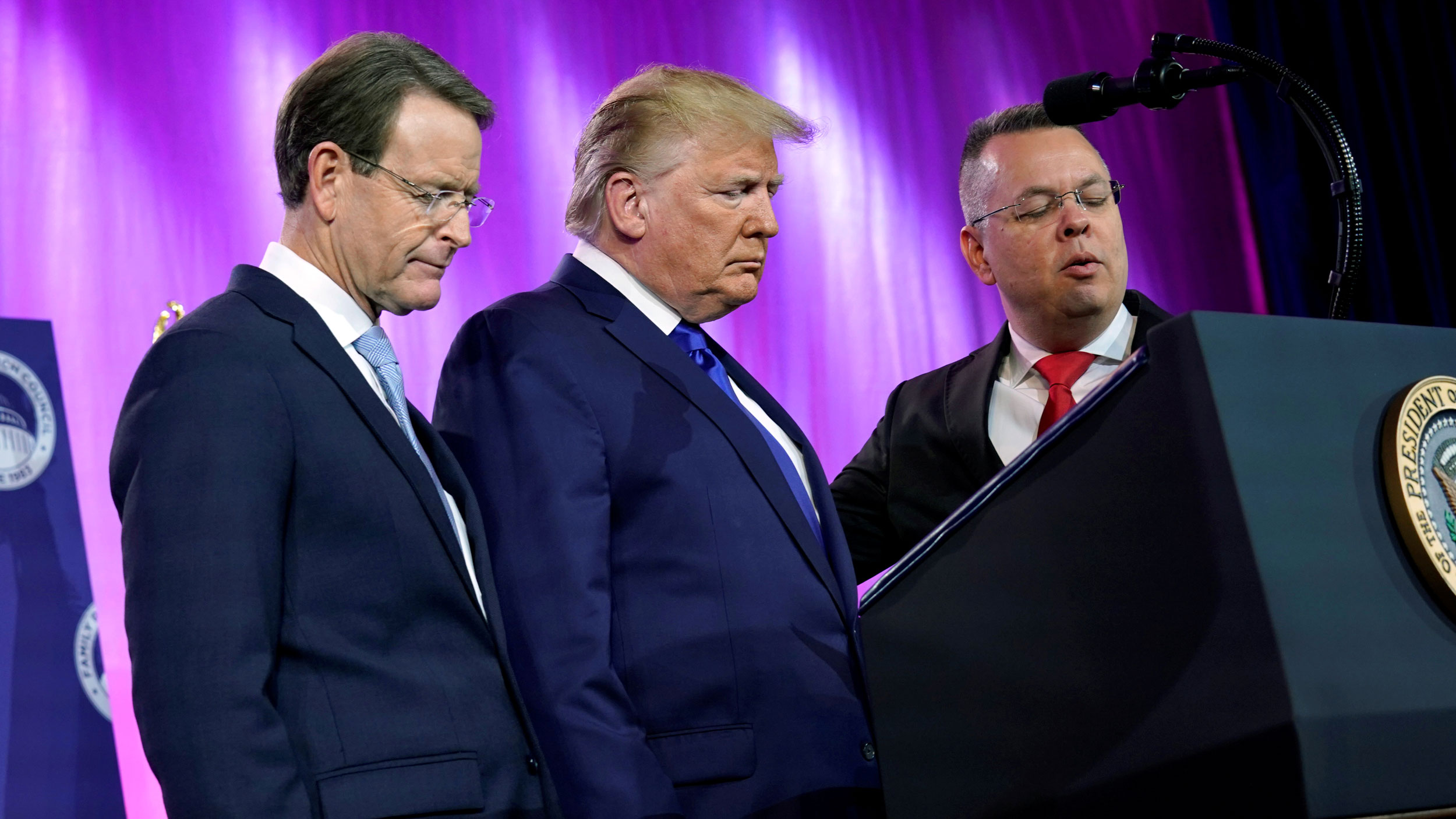 Three men in suits stand with their heads bowed.