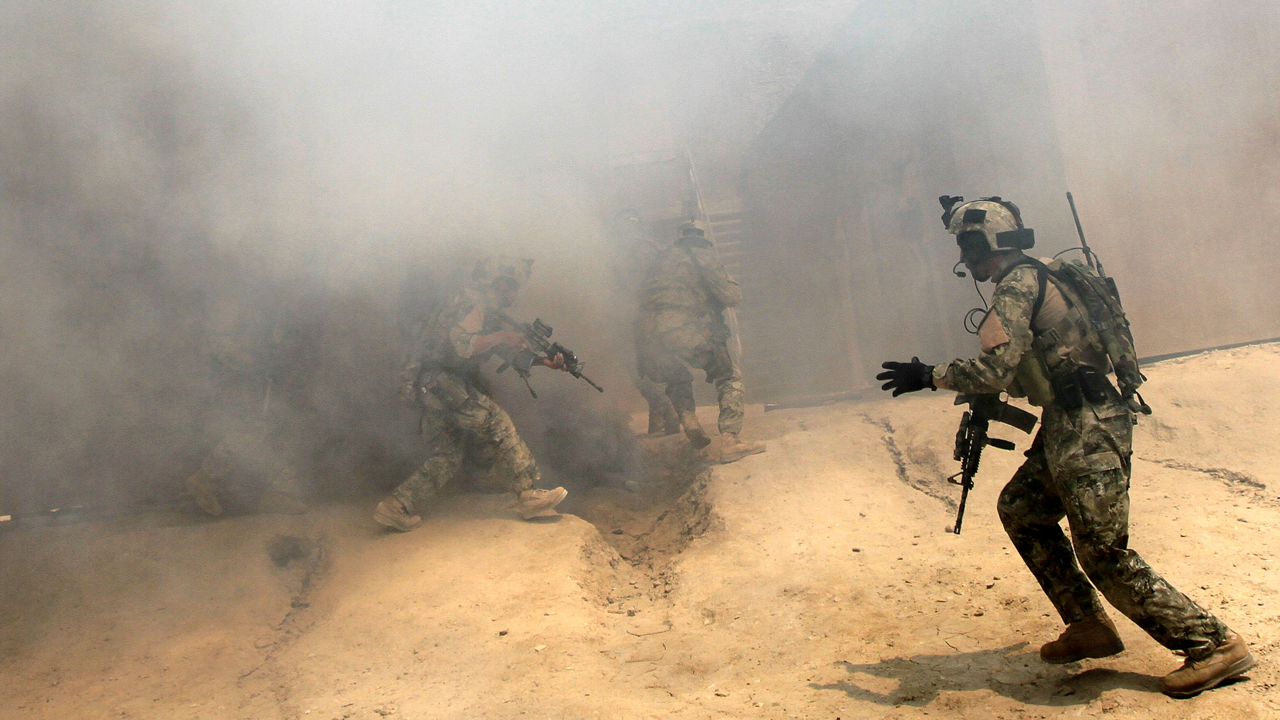 Men in military uniforms hold weapons and are walking into smoke inside building.