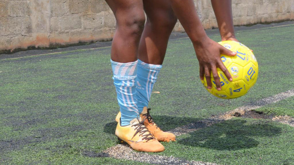 A woman's two feet and her hands are pictured as she holds a yellow soccer ball.