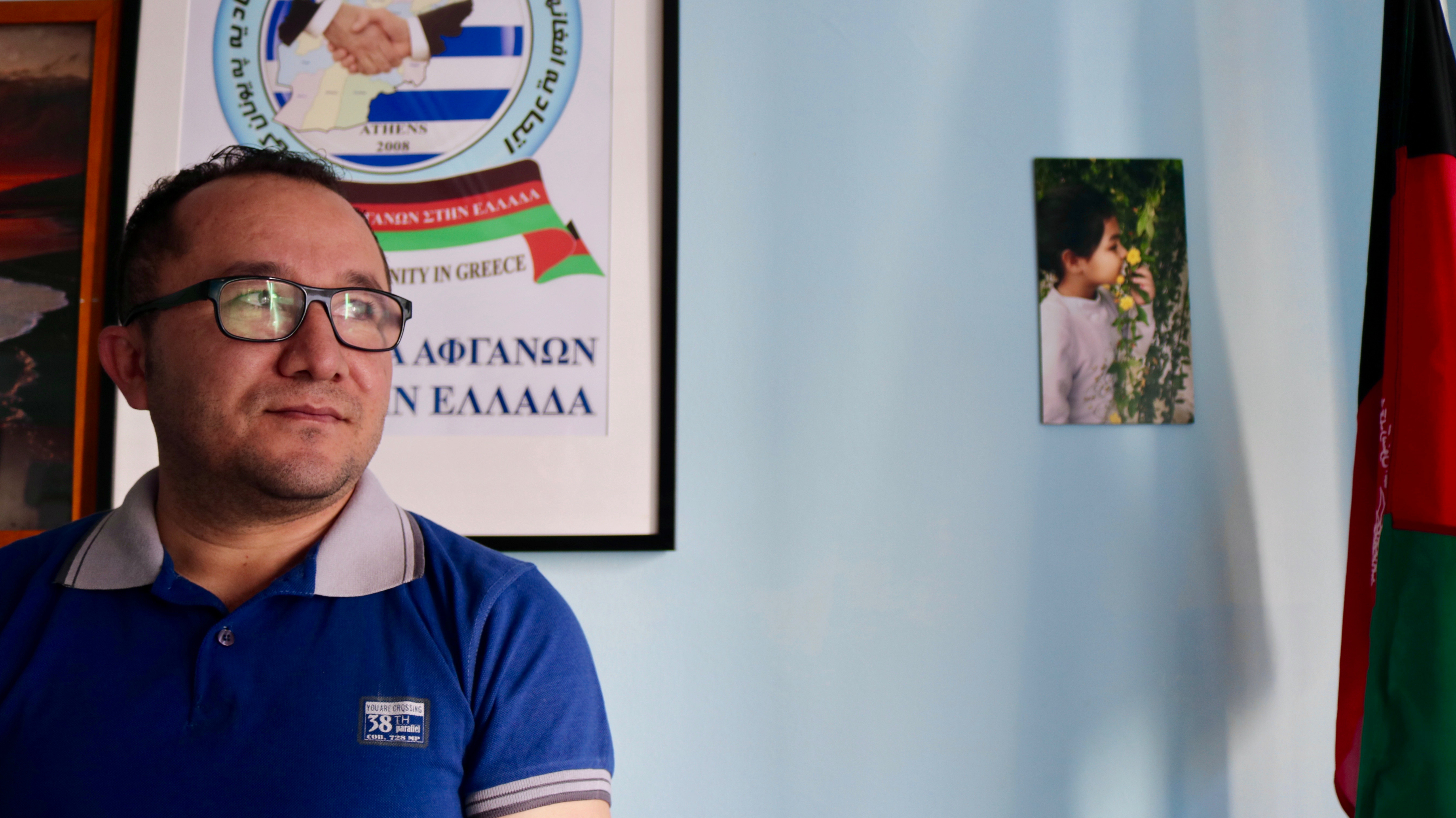 A man wears a blue shirt and glasses in an office