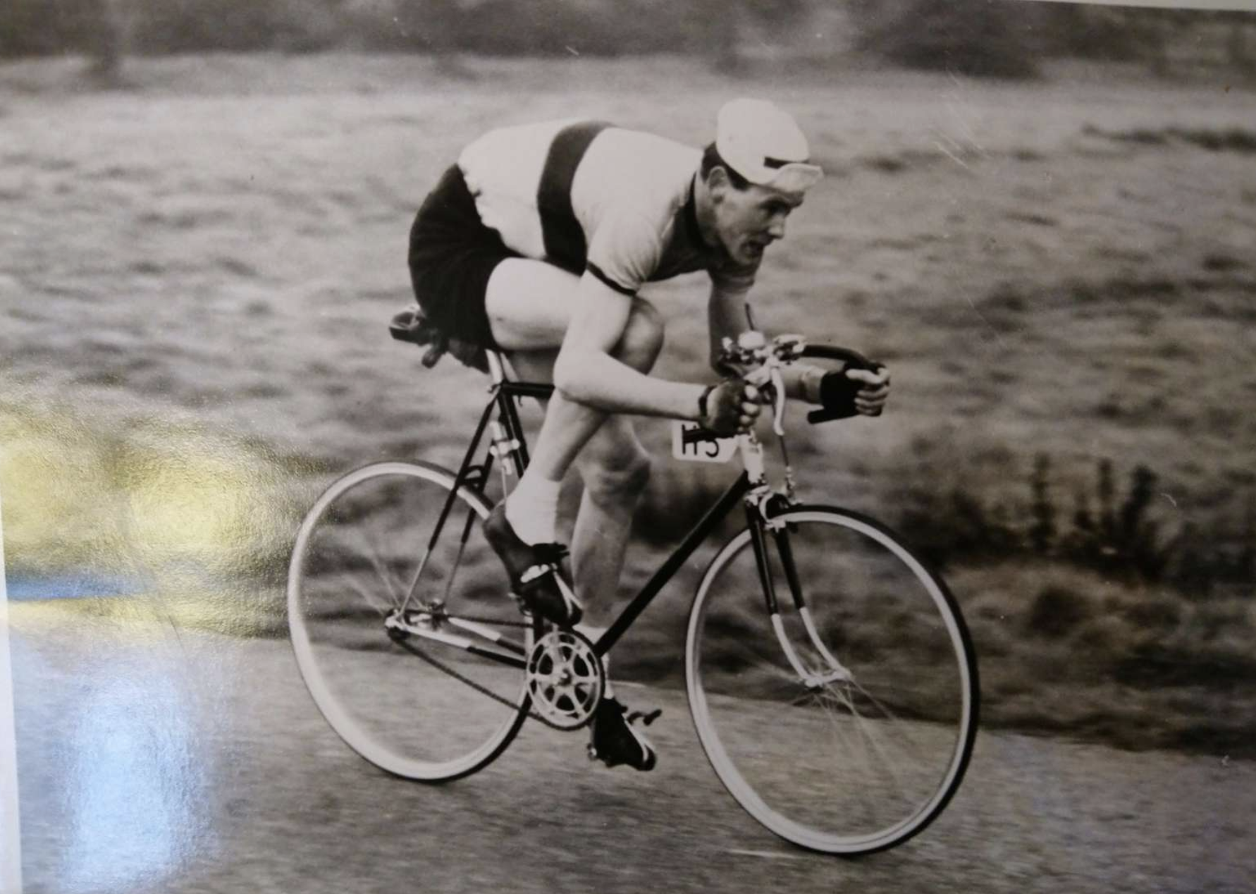 A man on a bicycle on a black and white photo.