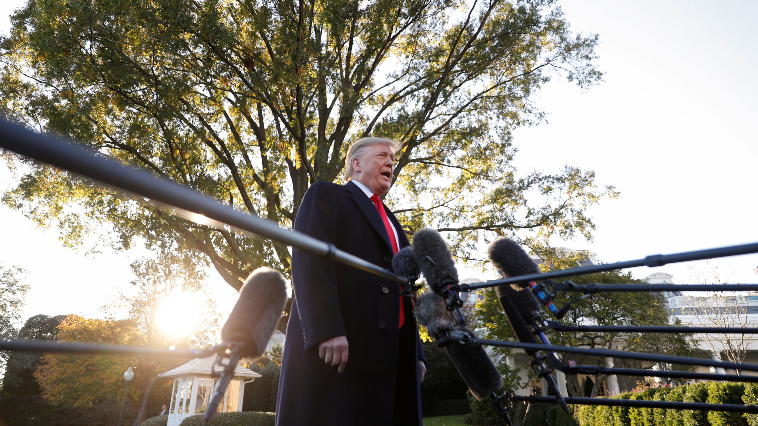 US President Donald Trump stands amid microphones outside