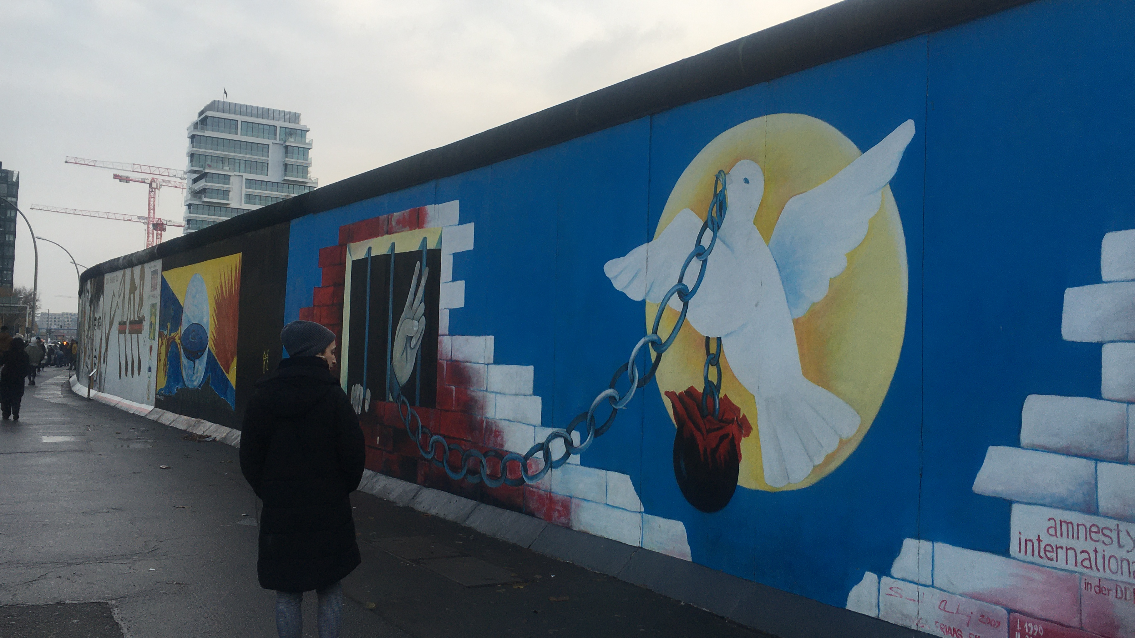 A mural of a white bird, chain and rose painted on the Berlin wall and a person walking by it