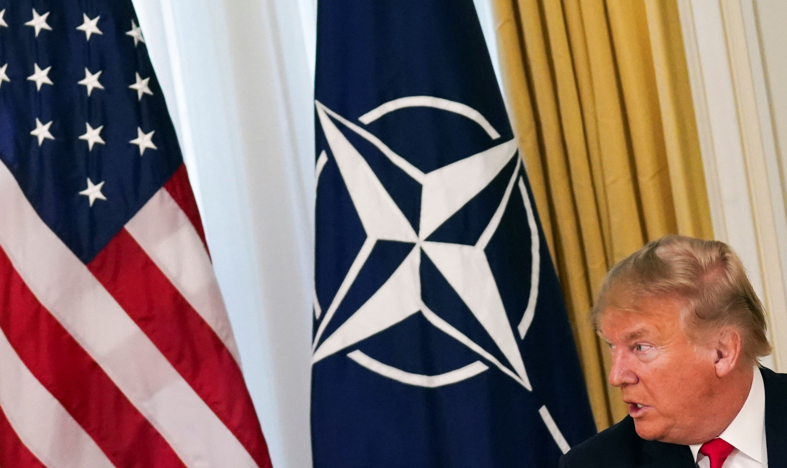 US President Donald Trump is shown looking to his right and sitting in front of the US and NATO flags.
