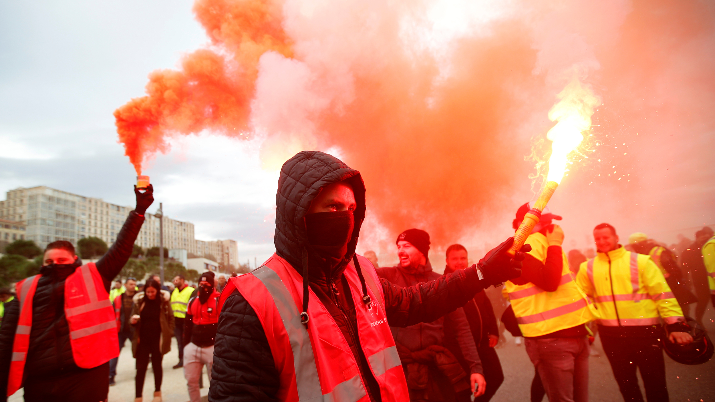 A group of protesters are shown wearing reflective vest and two men are holding bright road flares.