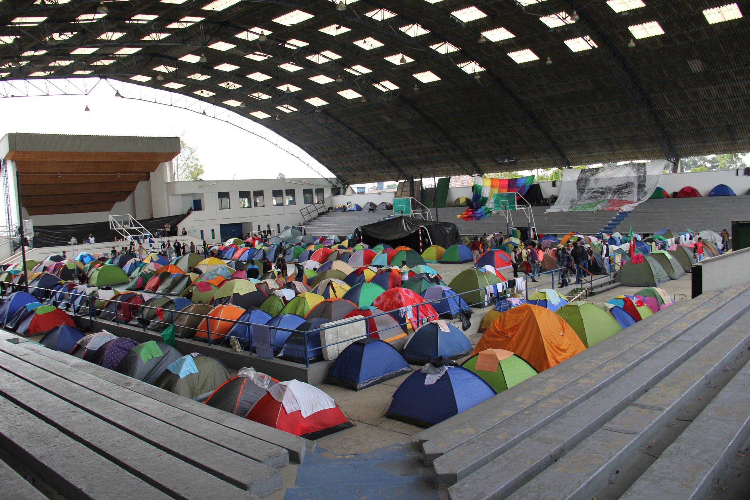 The floor of a stadium is filled with small pup tents.