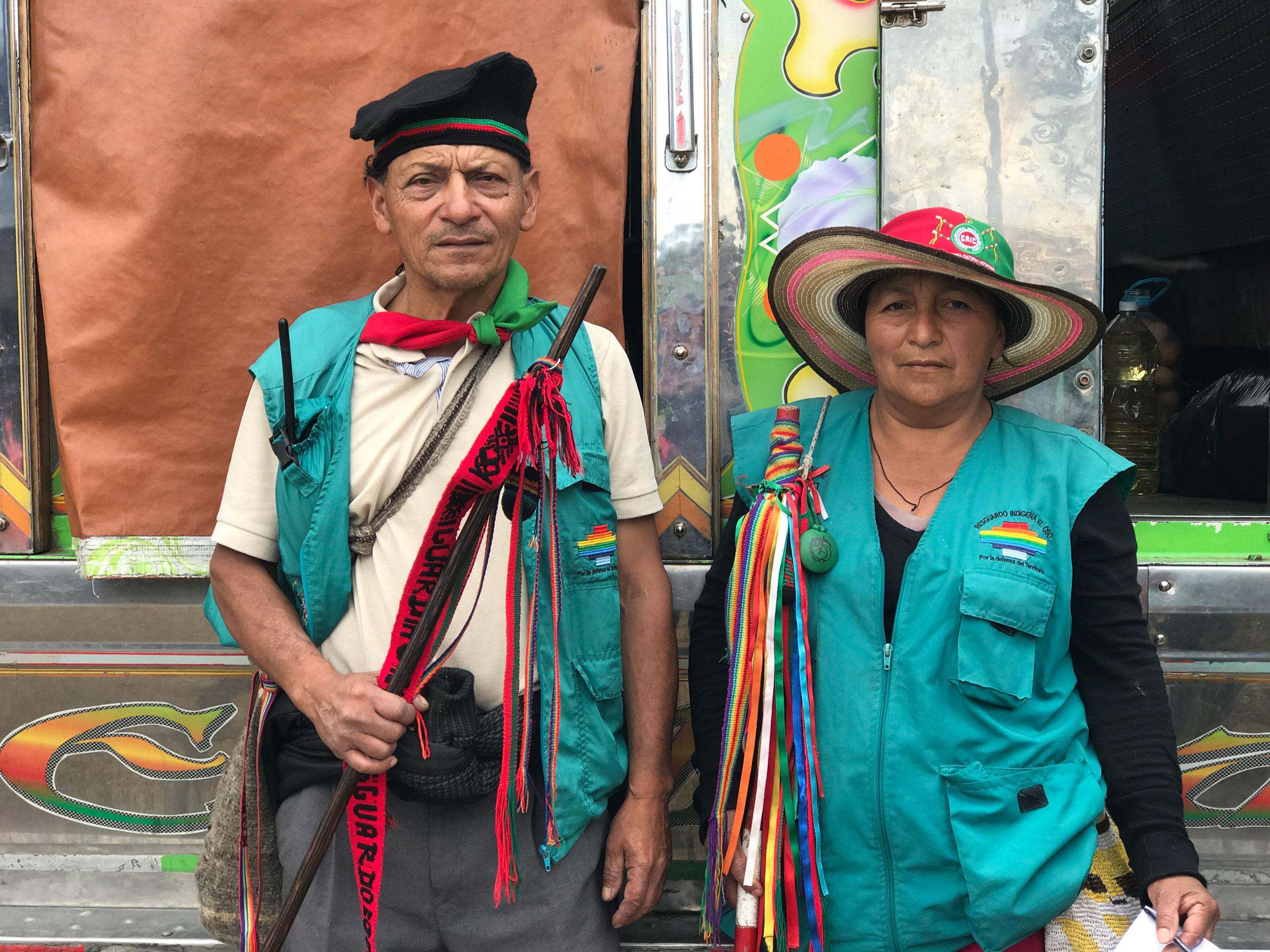An older Indigenous couple is shown both wearing green vests.