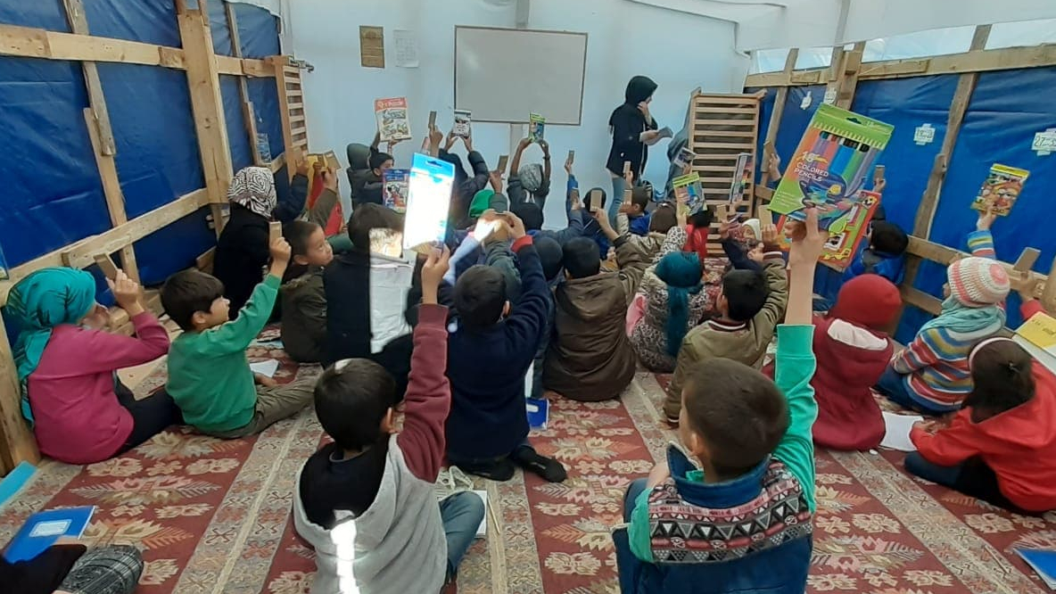 A group of children sit in on carpet inside room surrounded by blue tarp