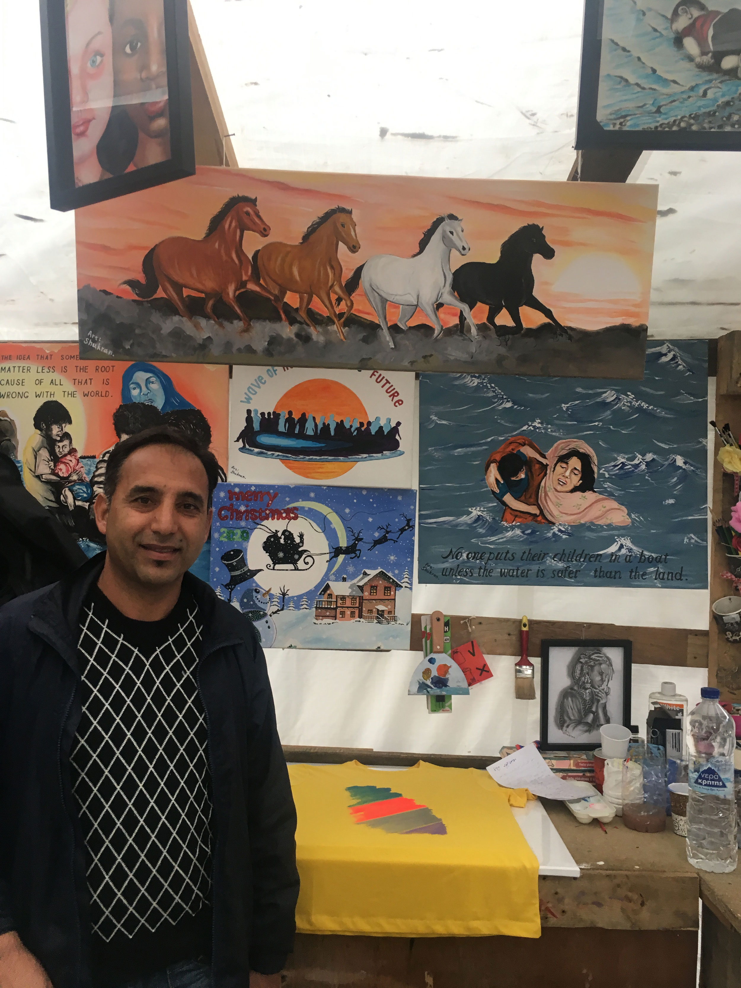 A man is shown standing in front of several pieces of art work including an illustration of four horses running.