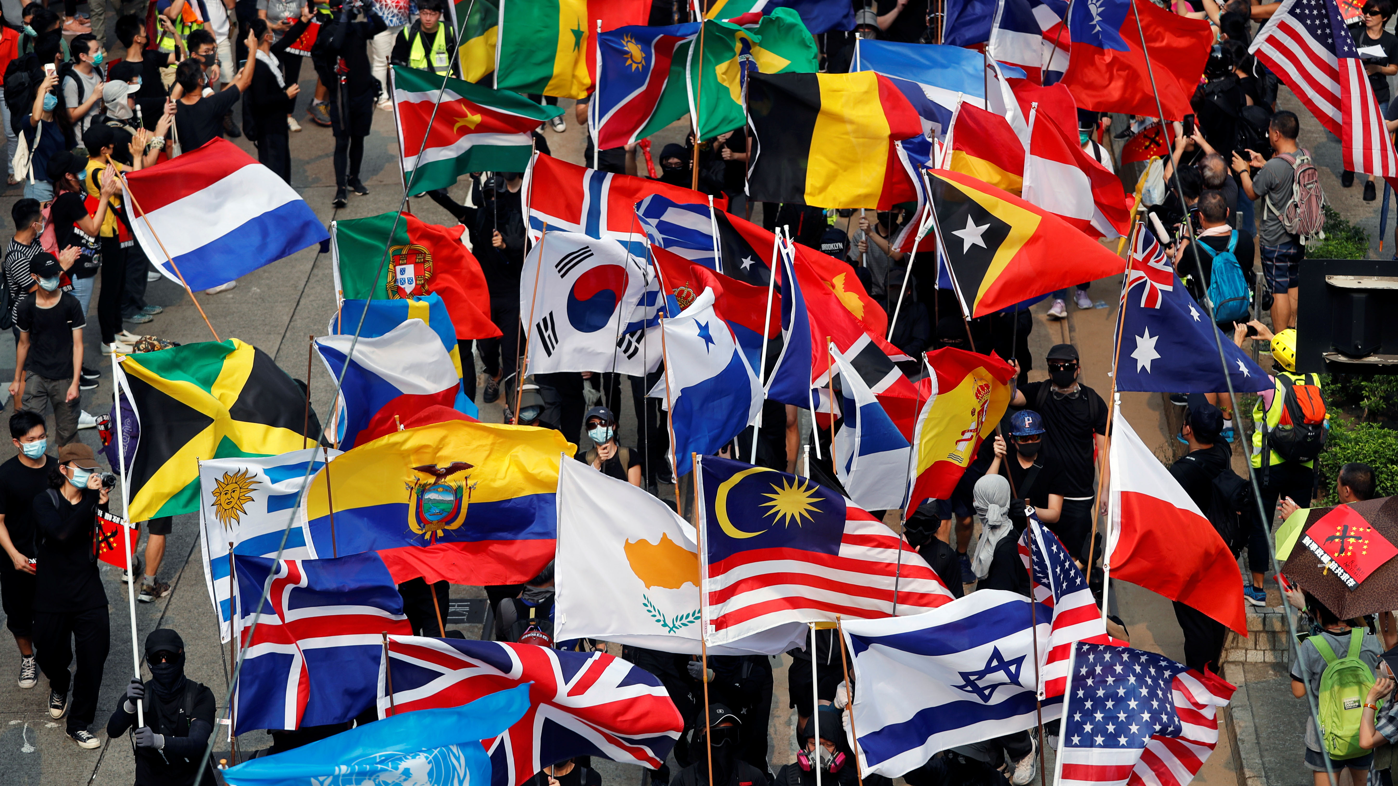 Flags of many countries carried by protesters fill the frame.