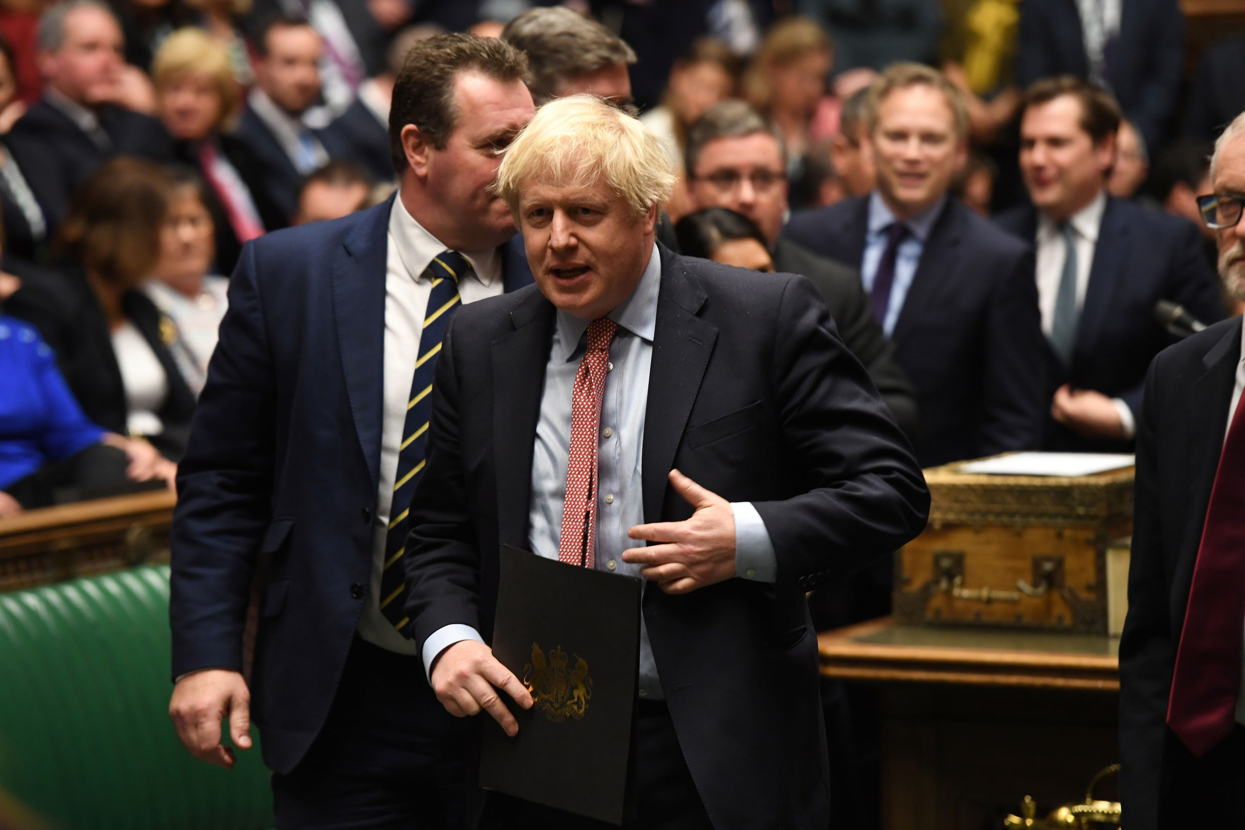 Britain's Prime Minister Boris Johnson is show walking with a folder in his hand and with several other lawmakers behind him.