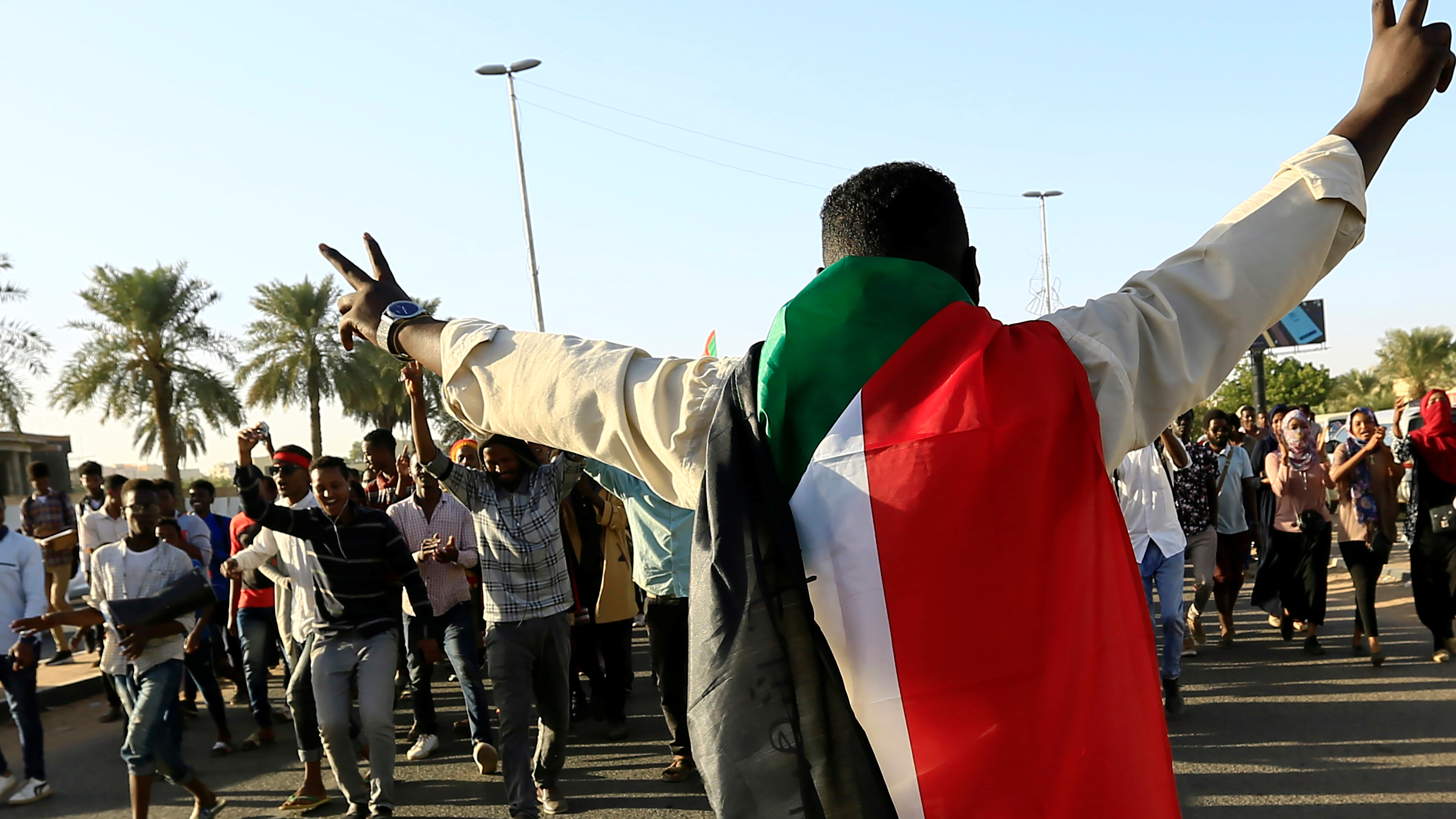 A protester holds peace sign and wears Sudanese flag across his shoulders