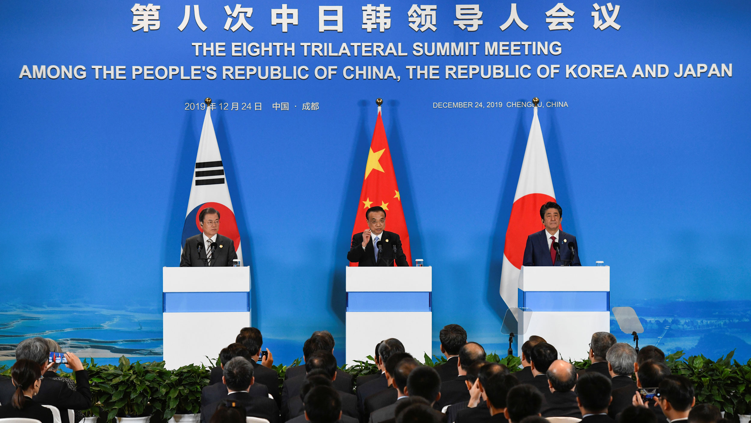 China's Premier Li Keqiang, Japan's Prime Minister Shinzo Abe and South Korea's President Moon Jae-in are shown standing behind three podiums with national flags.