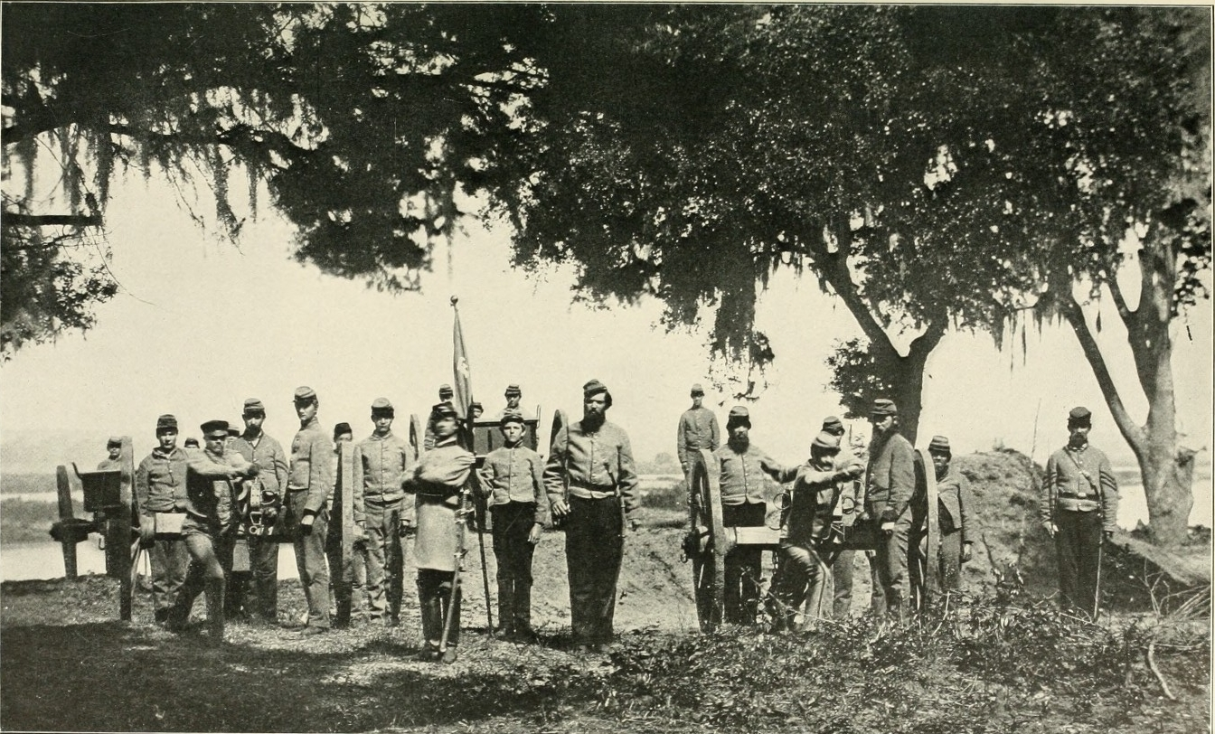 A group of military men stand in a line with their weapons.