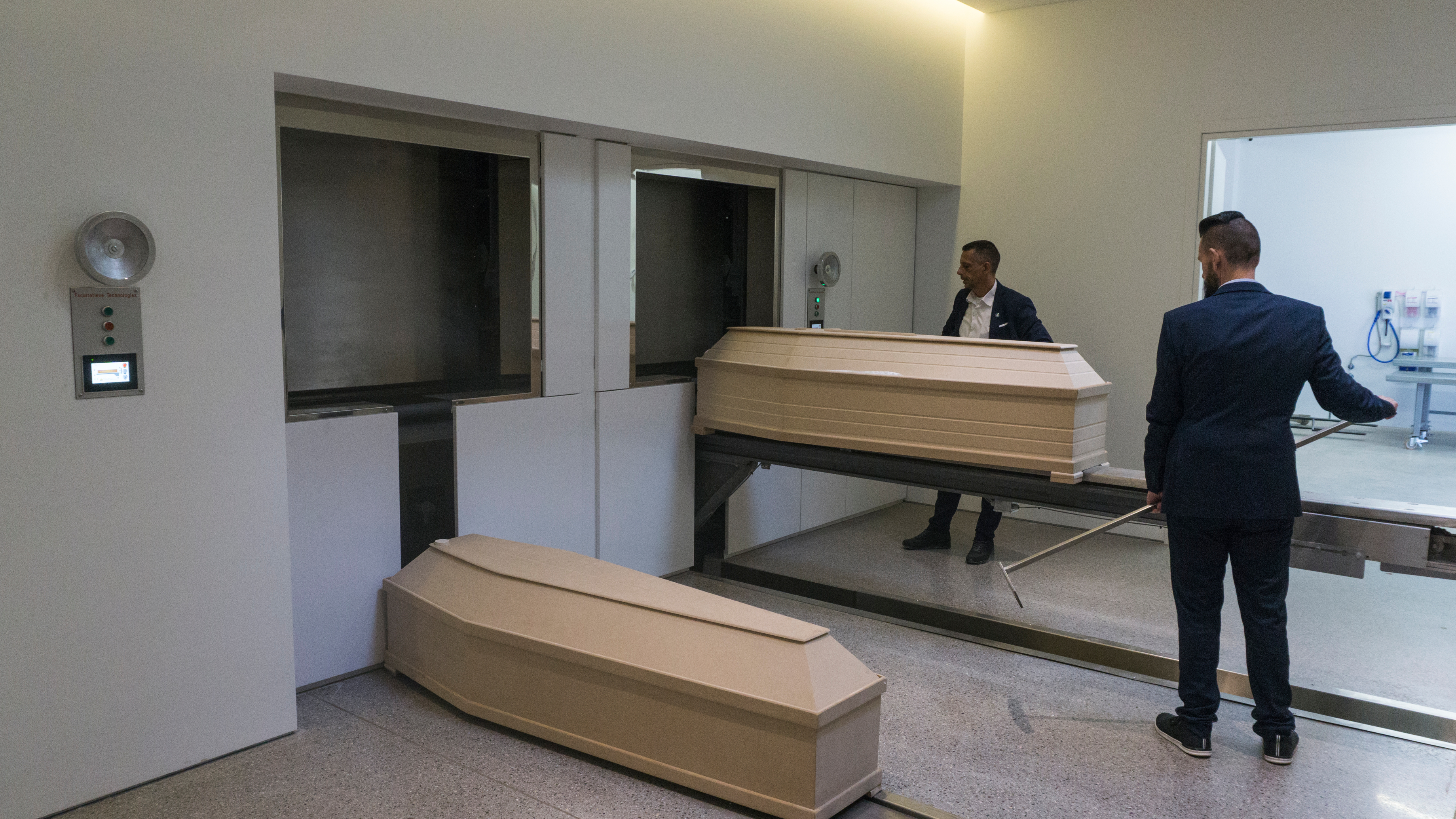 Two men in suits place beige-colored coffins in incinerators