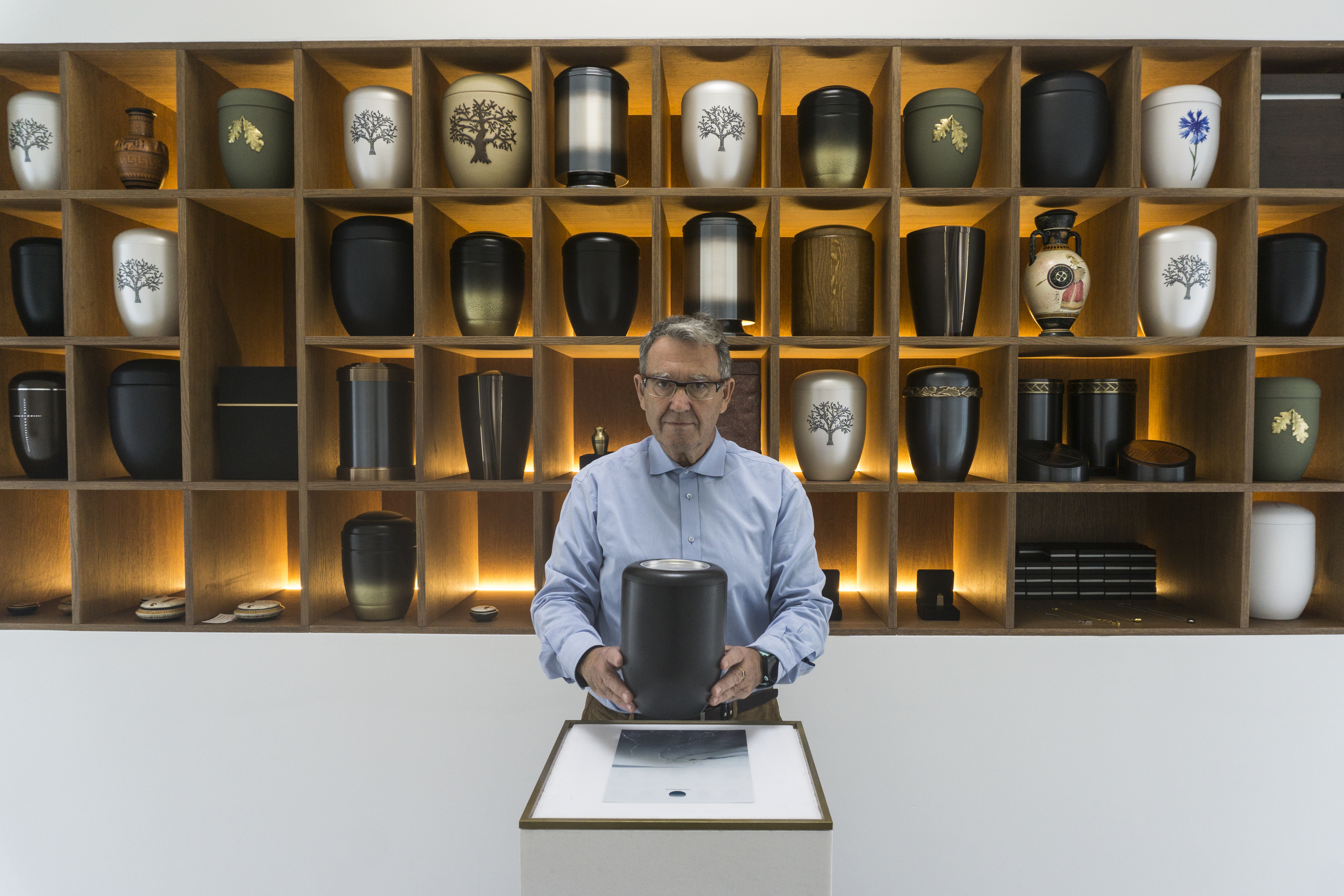 A man stands at a counter holding an urn with many urn designs behind him