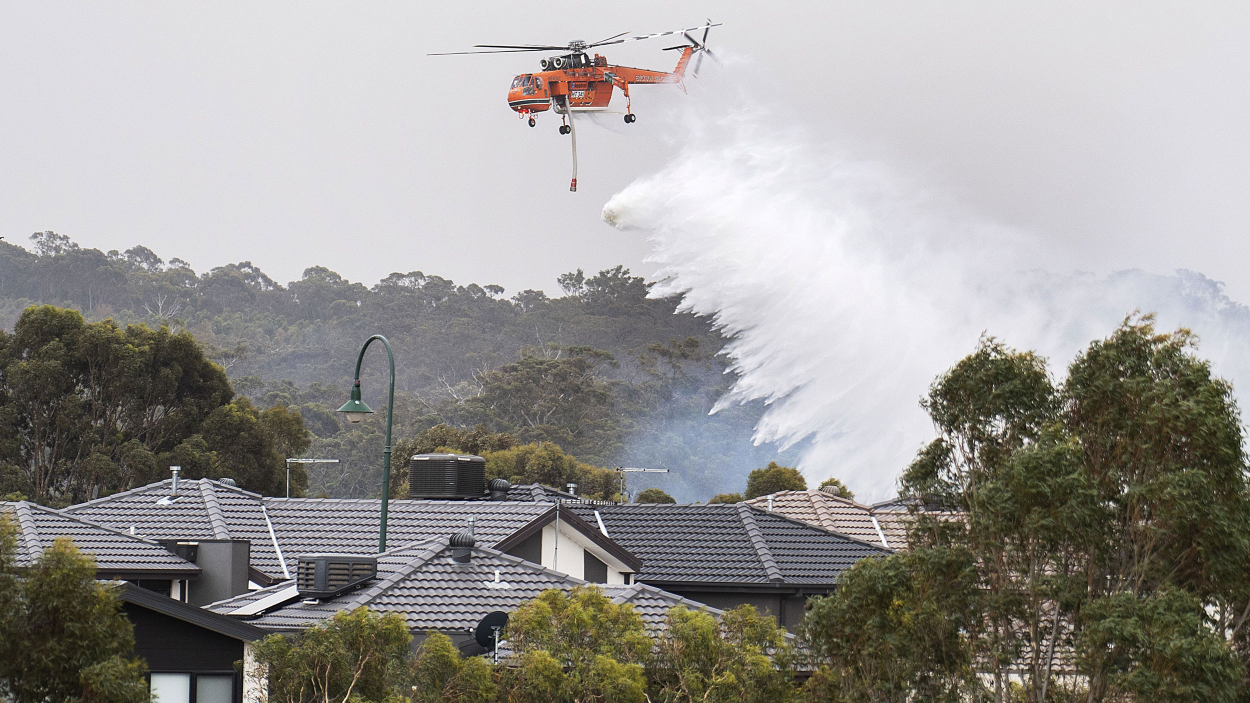 A large emergency helicopter is shown flying above several houses and dropping a large quantity of water.