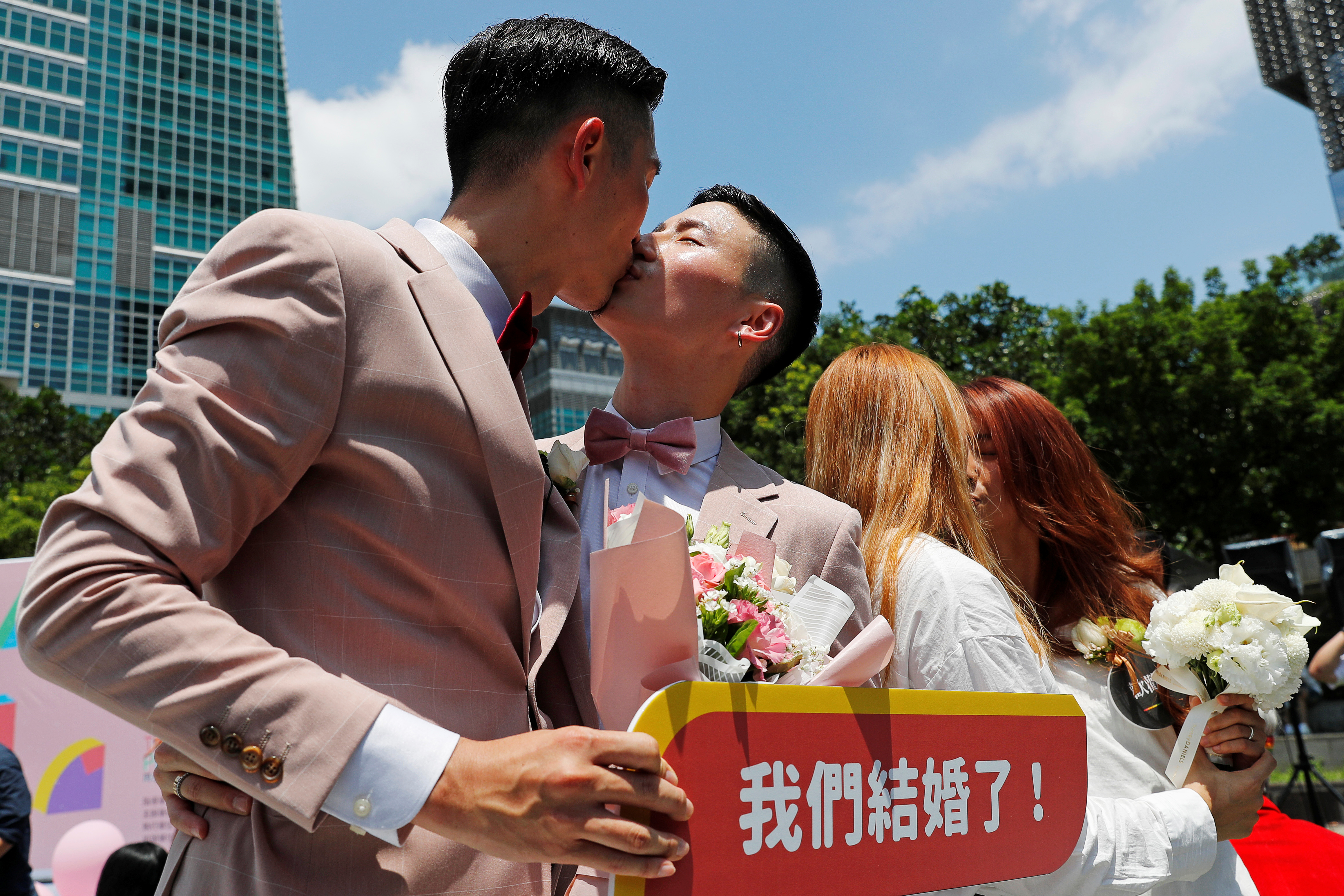 Gay and lesbian newlyweds kiss at a pro same-sex marriage party in Taipei.