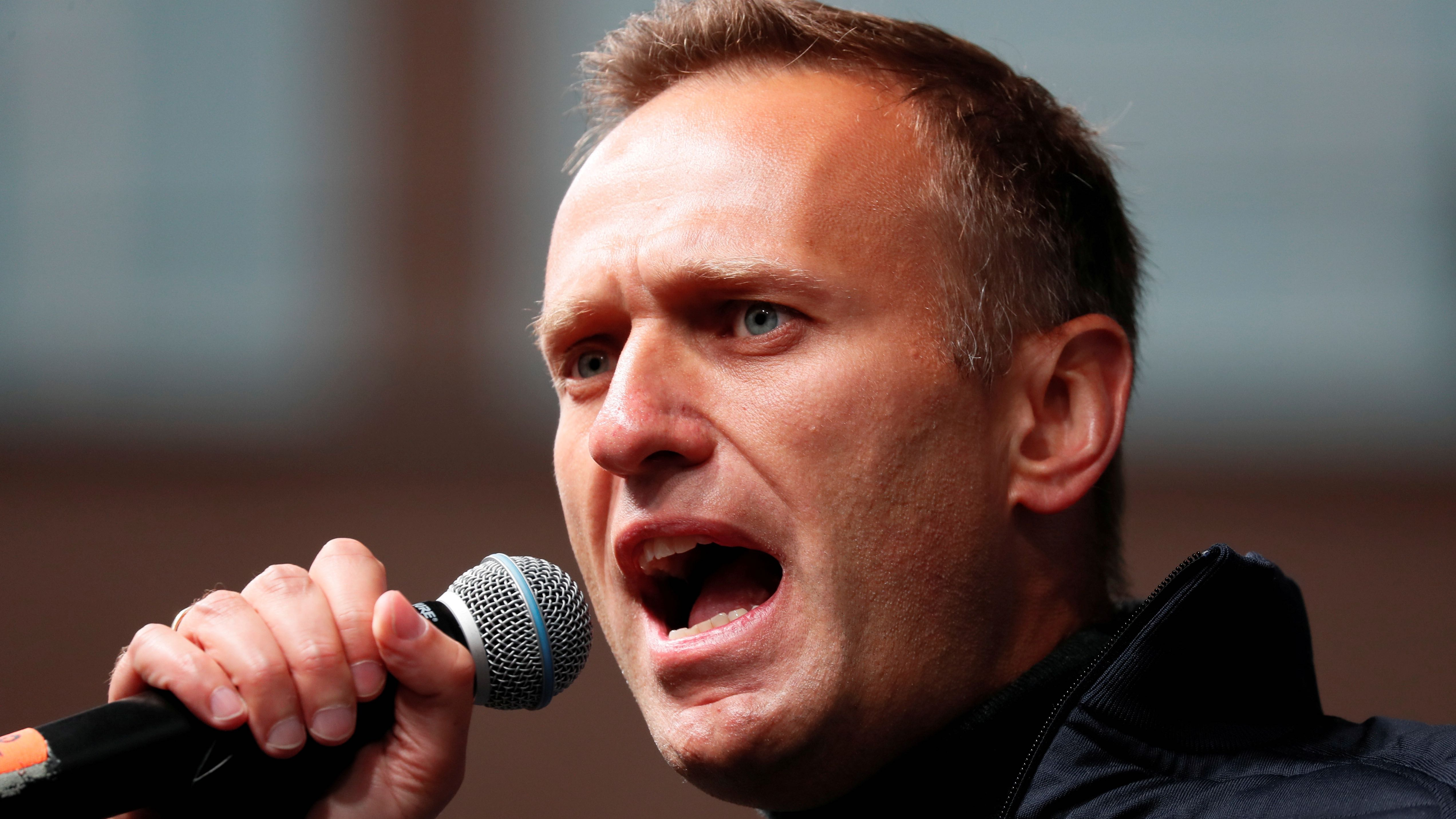 Navalny holds a microphone and speaks