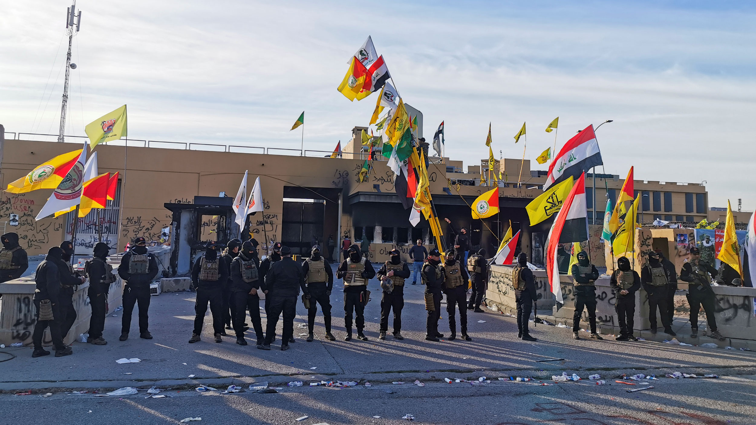 A line of security forces wearing helmets and carrying weapons are shown standing outside of the US Embassy in Baghdad.