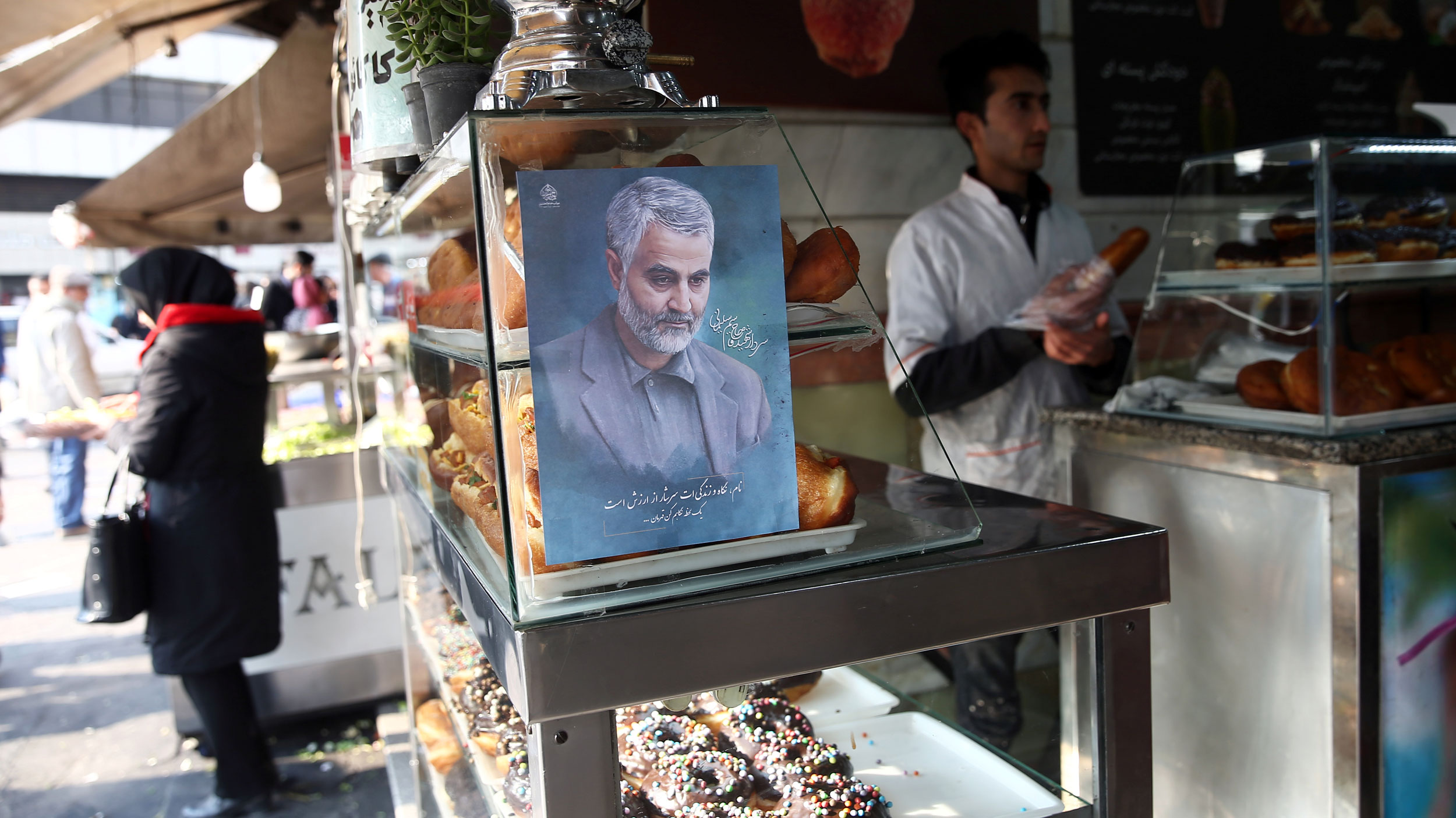 A portrait painint of of Iranian Maj. Gen. Qasem Soleimani is shown on a glass case in a confectionery shop.