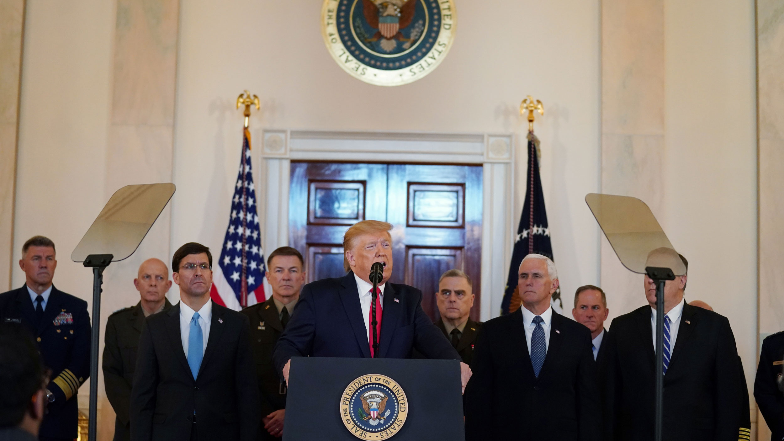 US President Donald Trump is shown speaking from a podium wearing a dark suit and red tie.