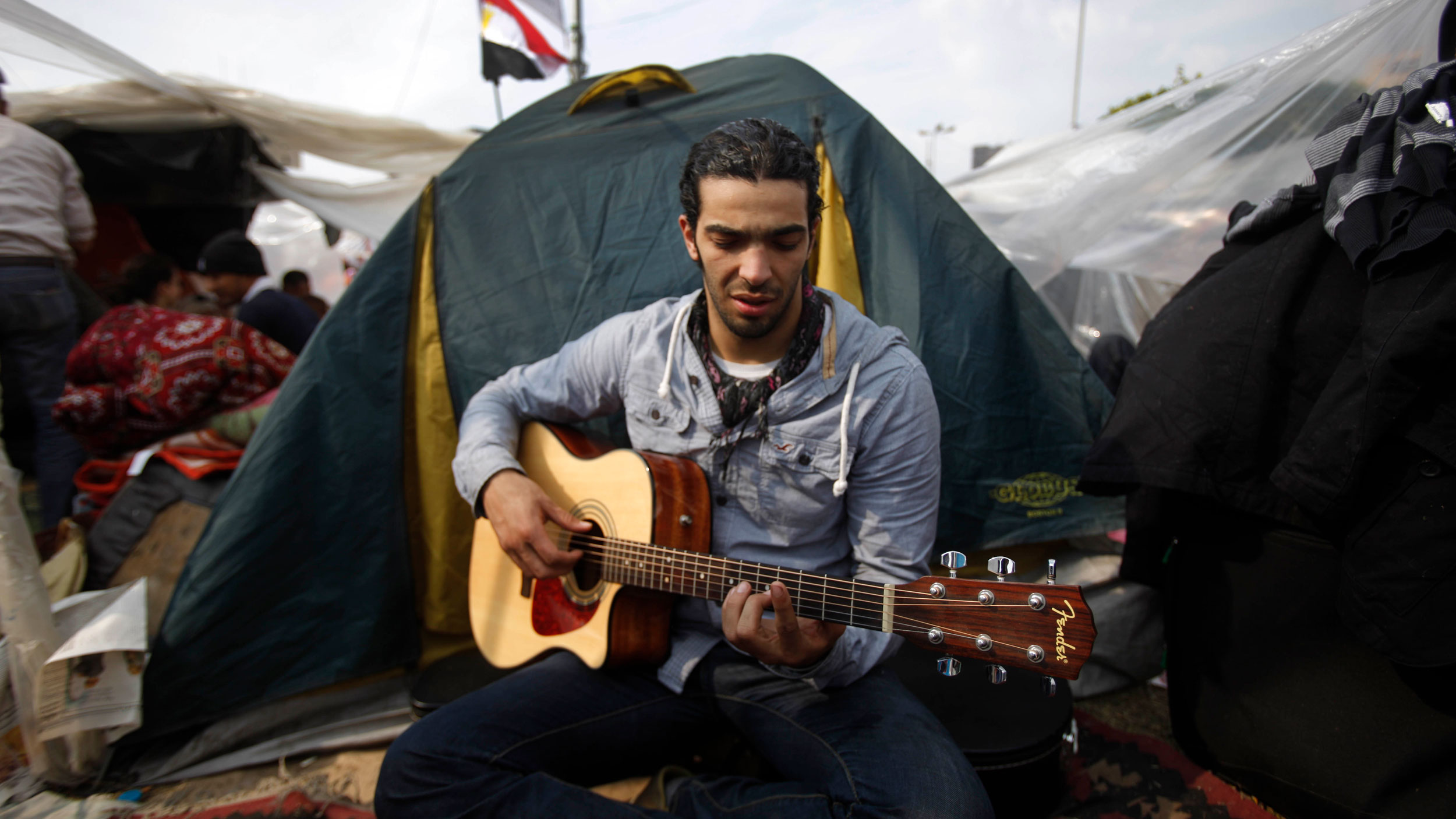 A man is sitting cross-legged in front of a tent and holding a guitar.