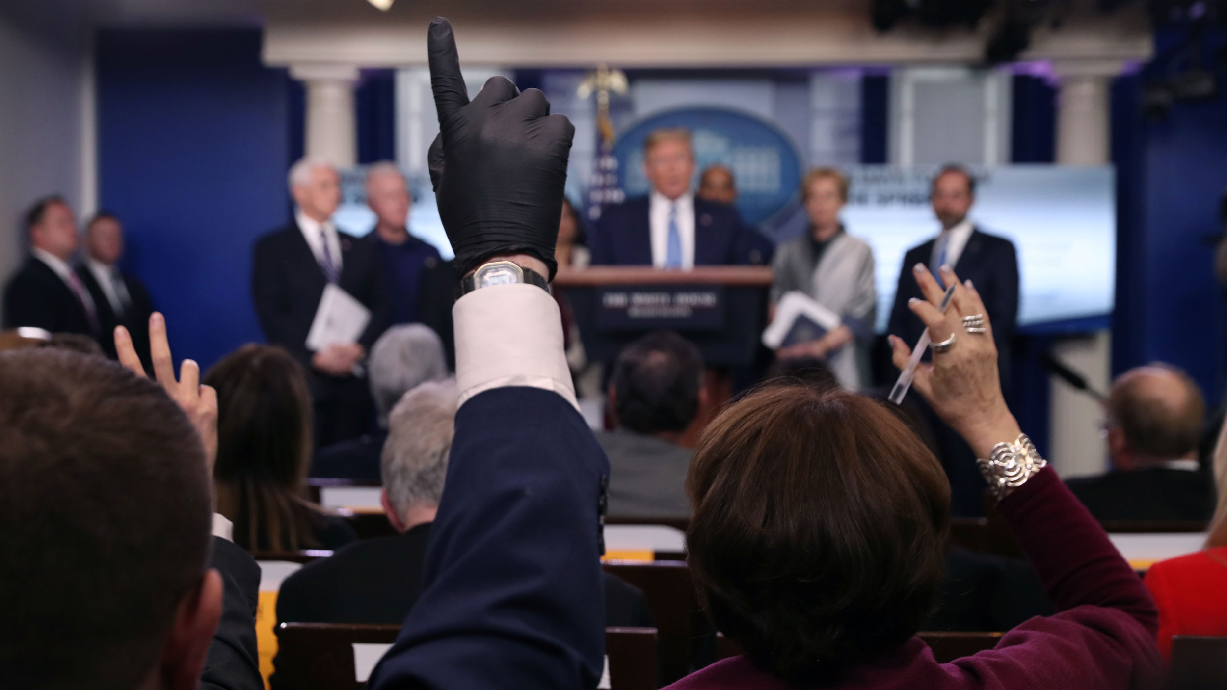 A group of reporters are shown sitting in chairs with one person holding up their hand which is covered by a dark colored latex glove.