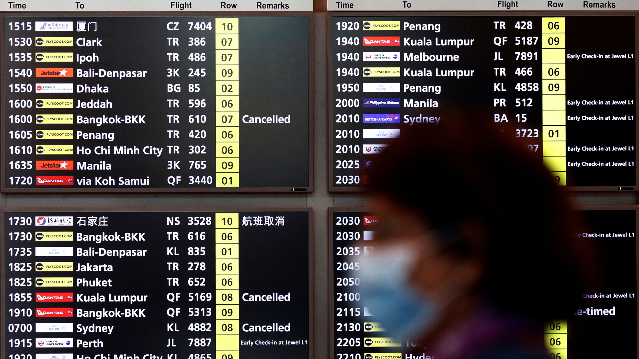 A woman wearing a mask passes is shown in soft focus with a arrivals and departures flight information board behind her.
